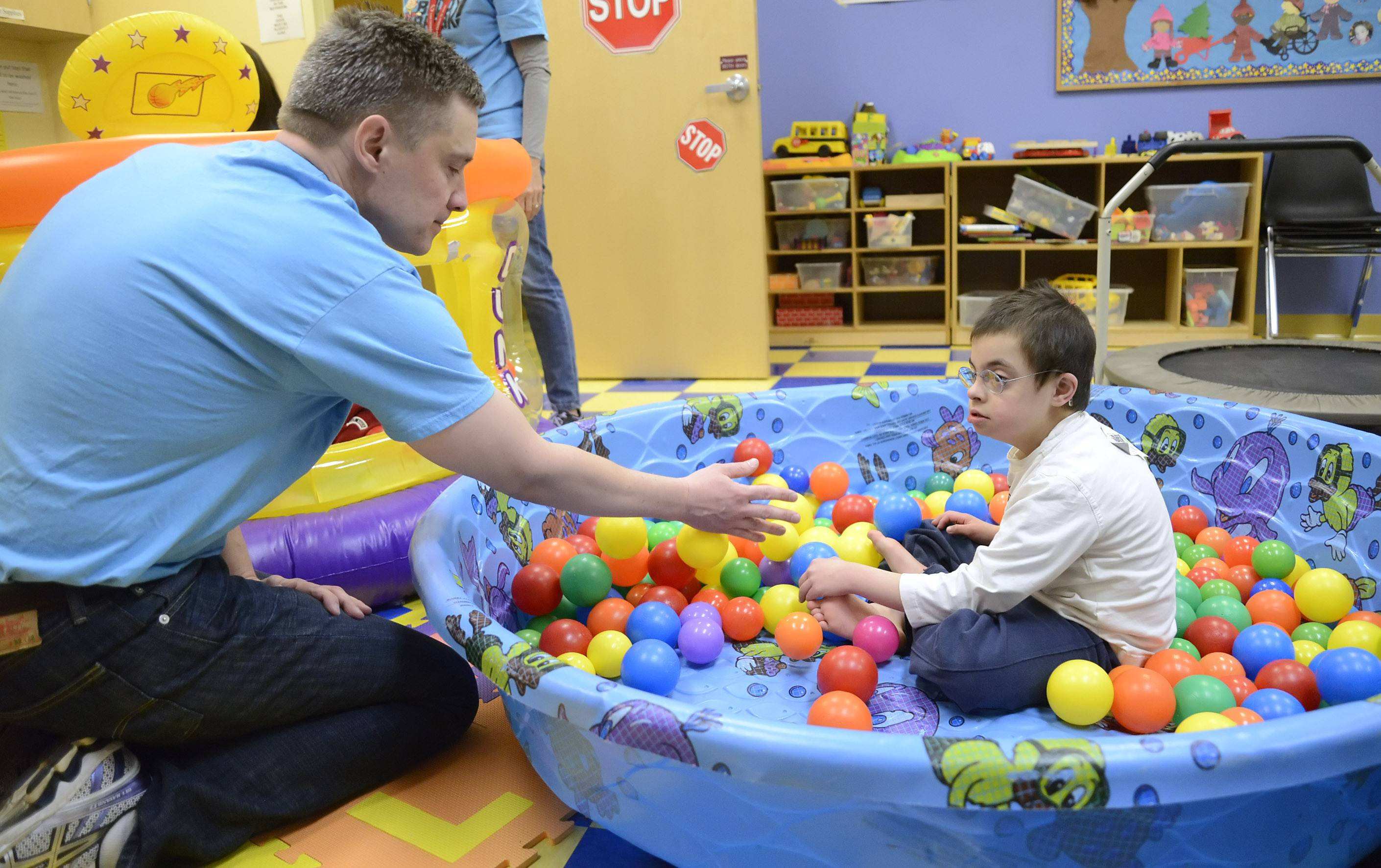 Keith Christophersen of Aurora helps pile up plastic balls in a pool for Michael Pavnica, 7, of Batavia, at a Nathaniel's Hope Buddy Break program at First Baptist Church in Geneva. Michael enjoyed kicking his legs, sending the balls flying through the air.