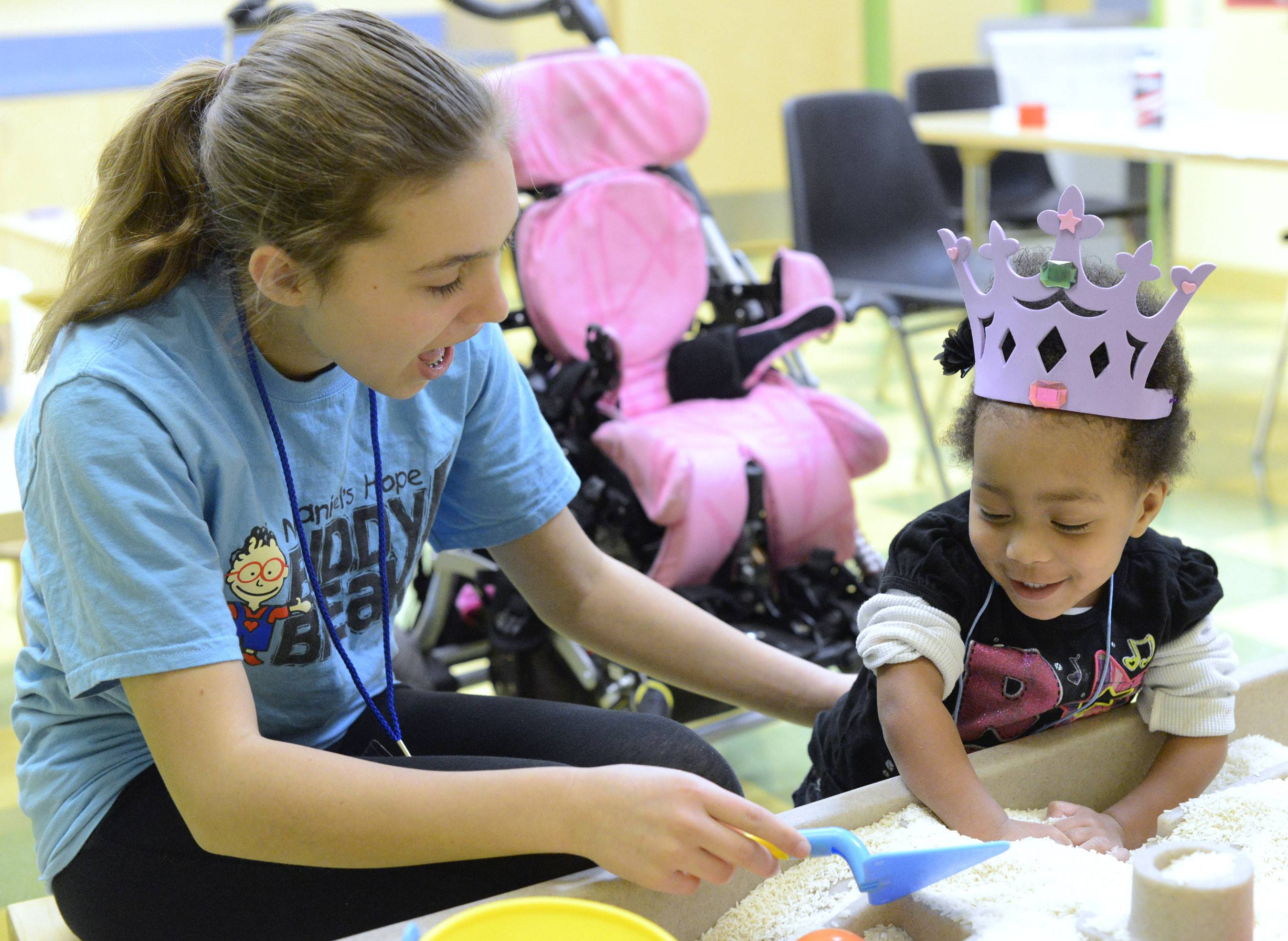 Rachel Christopherson, 13, of Aurora works with Kei'anna Bateman of Kaneville playing at a rice table during a Nathaniel's Hope Buddy Break program at First Baptist Church in Geneva. Kei'anna uses a wheelchair, and having her stand at the table helps her use her support herself and strengthen her legs.