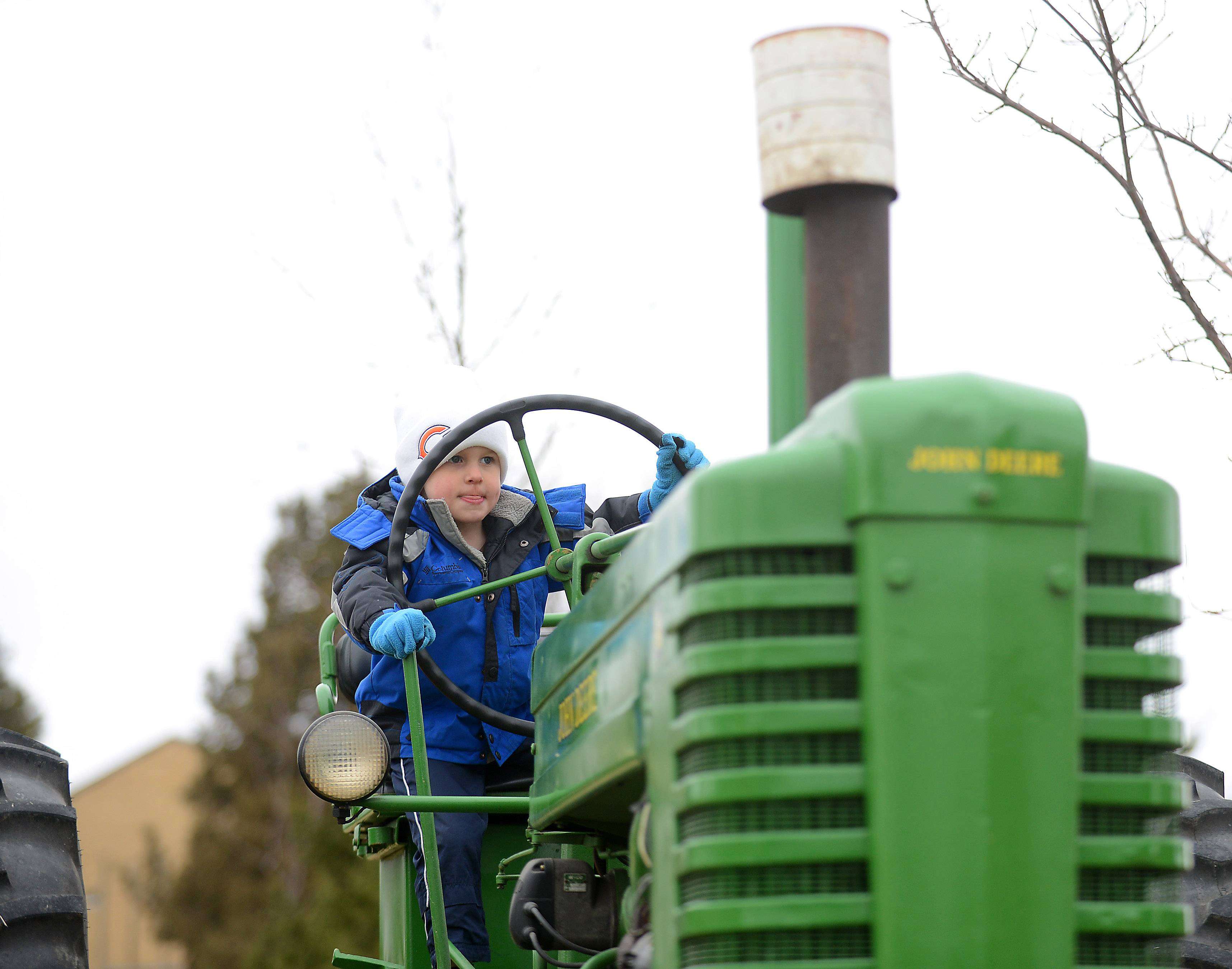 Tyler Bradley, 4, of St. Charles, takes the wheel of a 1947 John Deere tractor at the Kane County Farm Bureau Touch a Truck event in St. Charles Friday.