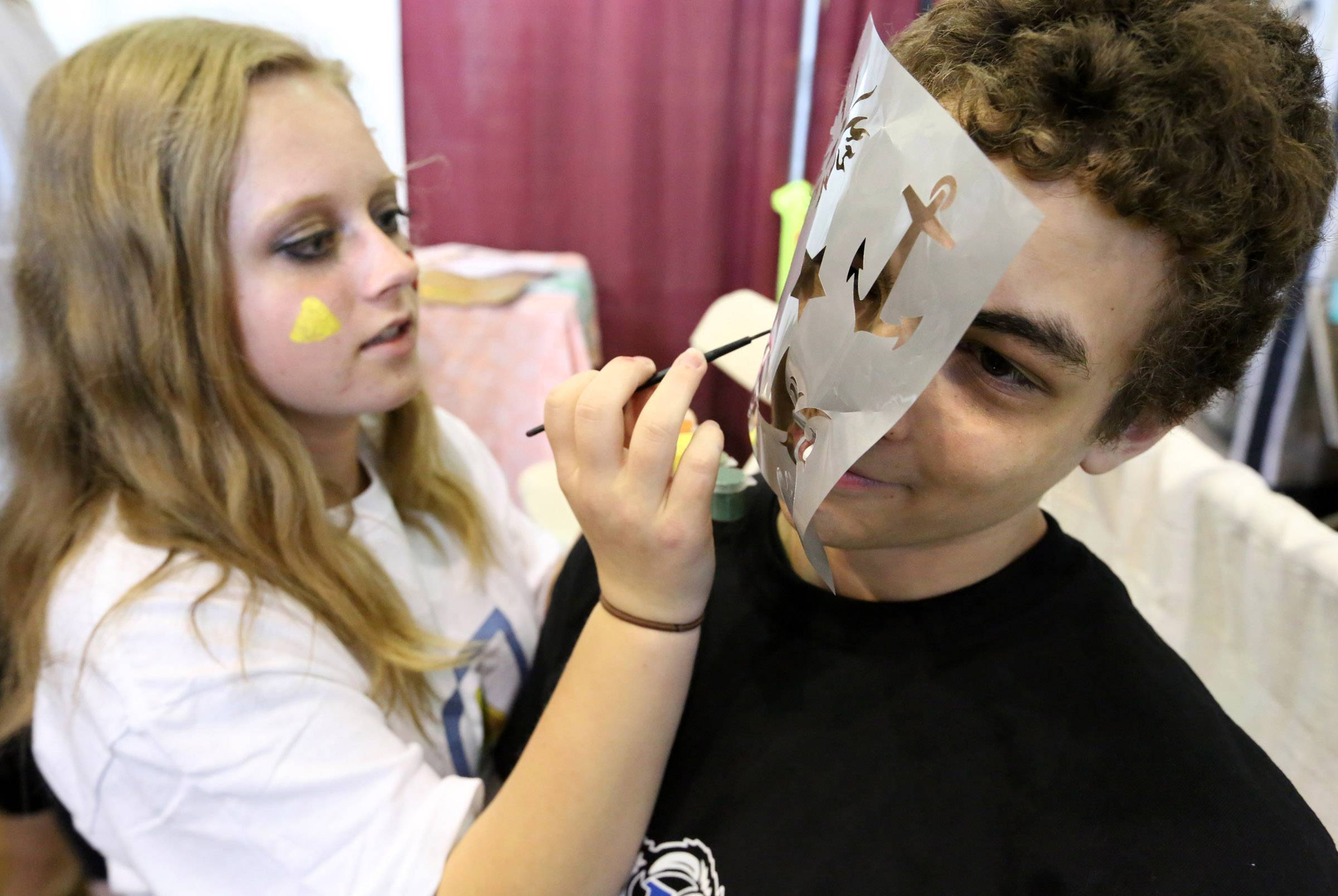 Brian Borcean, 16, has his face painted by Suzanne Zborowski, also 16, both of Lake Zurich, using a stencil at Be Safe Driving School's booth at Lake Zurich's annual Business and Community Showcase on Saturday at Lake Zurich High School. Zborowski is a graduate of the driving school.