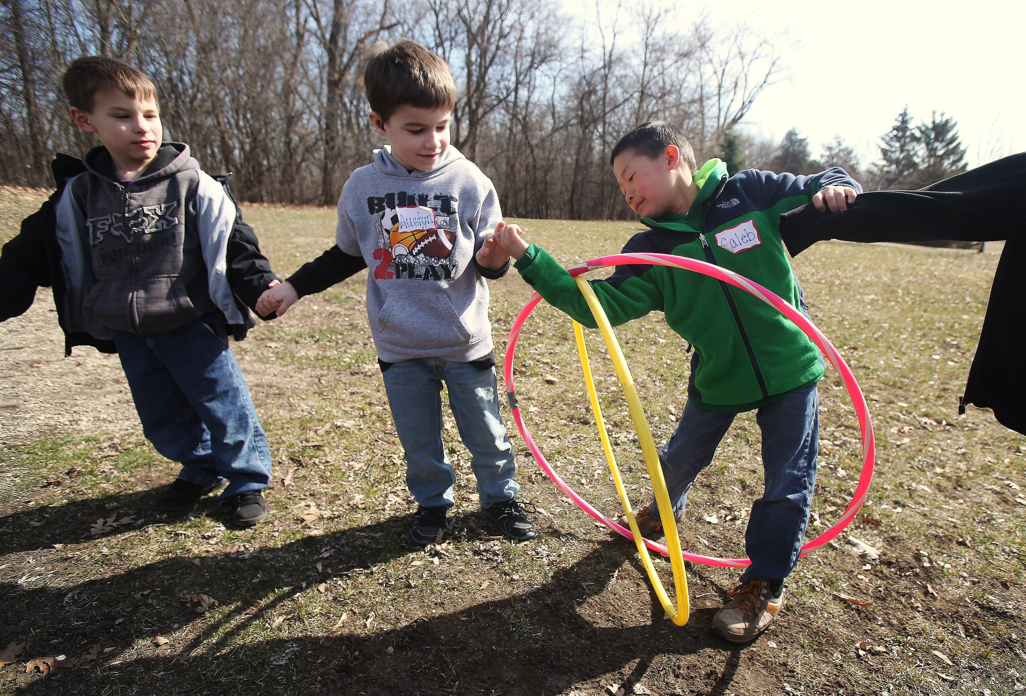 Eight-year-old Caleb Lee, of Vernon Hills, right, tries to go through two hoops as he plays a game with Austyn Hunt, 7, of Ingleside, and Alex Maritz, 5, of Antioch, during team building day for hearing impaired children Sunday at Camp Duncan in Ingleside. Forty-five kids played games and intermingled during the event sponsored by the SEDOL Foundation.
