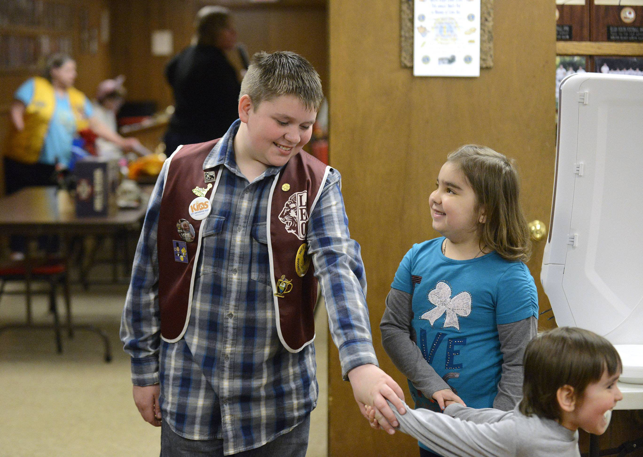 Maria Serban, 6, smiles up at Dylan Snyder, 11, as they play with her younger brother, Victor, 3 1/2, after Dylan presented Maria and her mother, Elena, with a check for almost $4,000 at the South Elgin Lions Club on Wednesday. All live in South Elgin. Maria, a first grader at Willard Elementary School, has a rare form of arthritis and she's was very sick the past few months. Dylan, a fifth grader at the school, raised funds with a  spaghetti dinner and auction last month at the Lions club, where his great grandfather, Leo Snyder, is a member.
