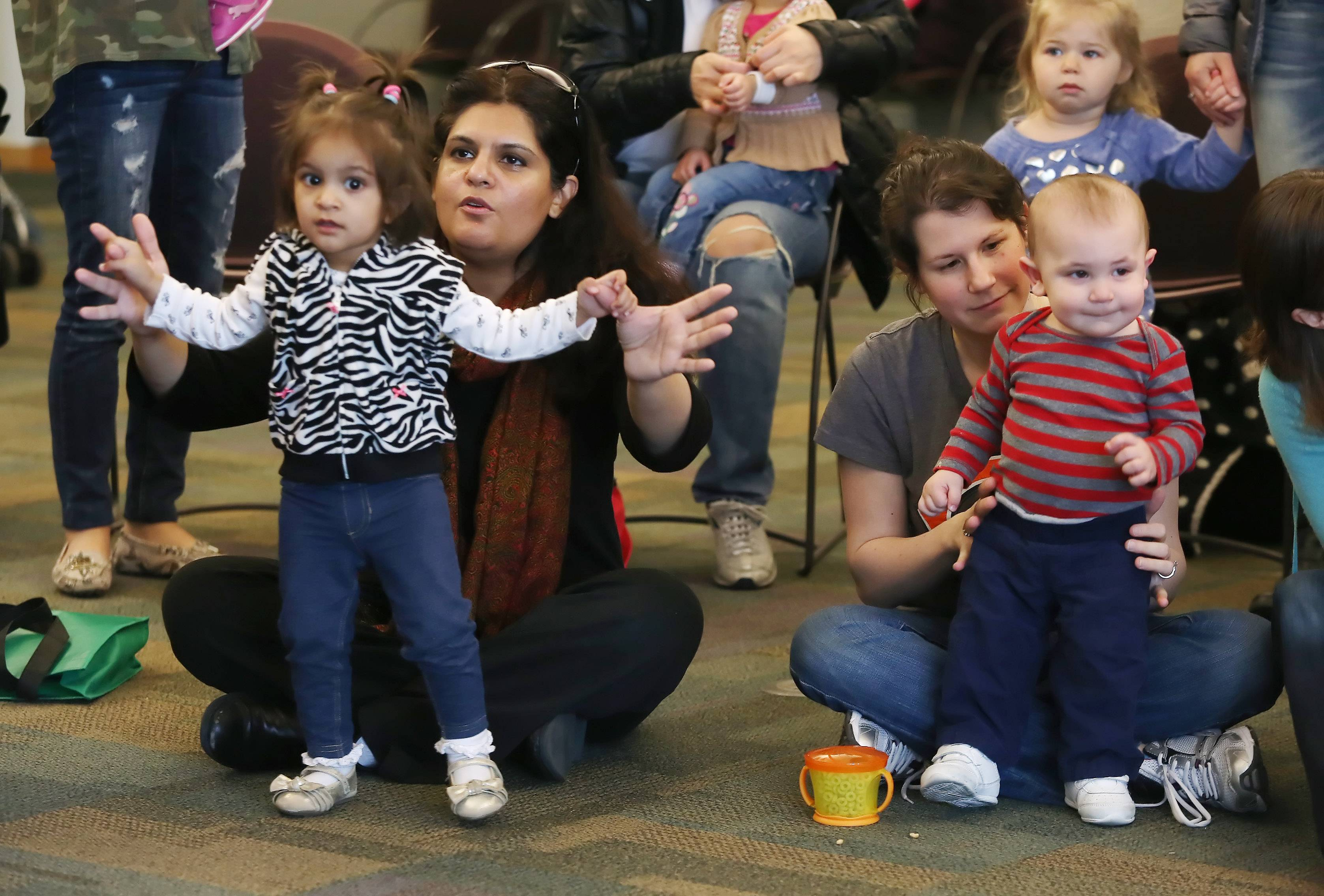 Samira Syed, left, of Vernon Hills, with her daughter, Shifa, 20-months-old, and Jamie Schillinger, of Buffalo Grove, with Clark, 1, dance to a song during the Giggles & Wiggles kids music program at Vernon Area Public Library in Lincolnshire. The kids music program is for children 15-24 months and helps them connect with sounds, dance, and music.
