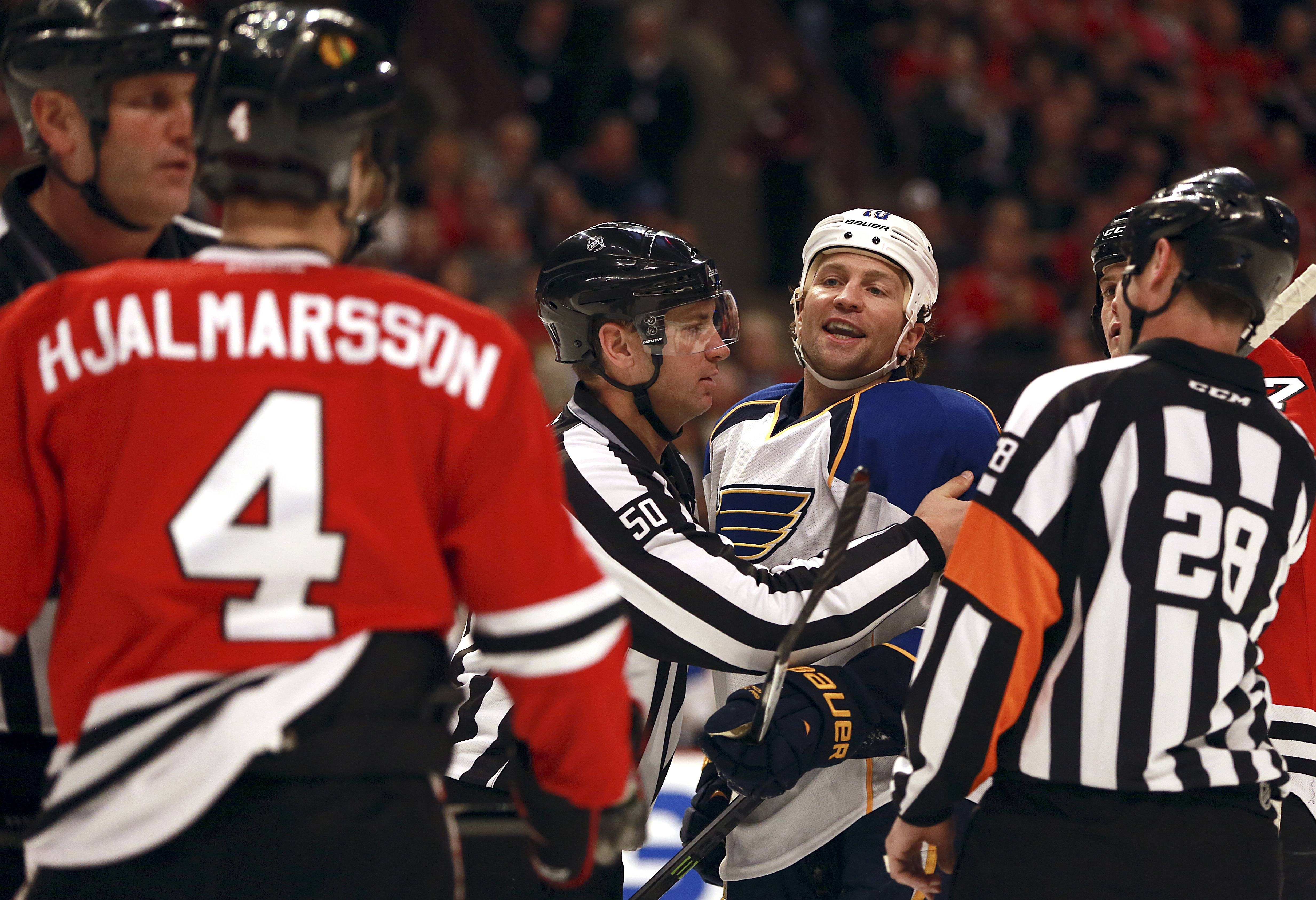 Blackhawks' Niklas Hjalmarsson (4) and St Louis Blues' Brenden Morrow, center right, get separated during the first period of an NHL hockey game in Chicago on Sunday, April 6, 2014.