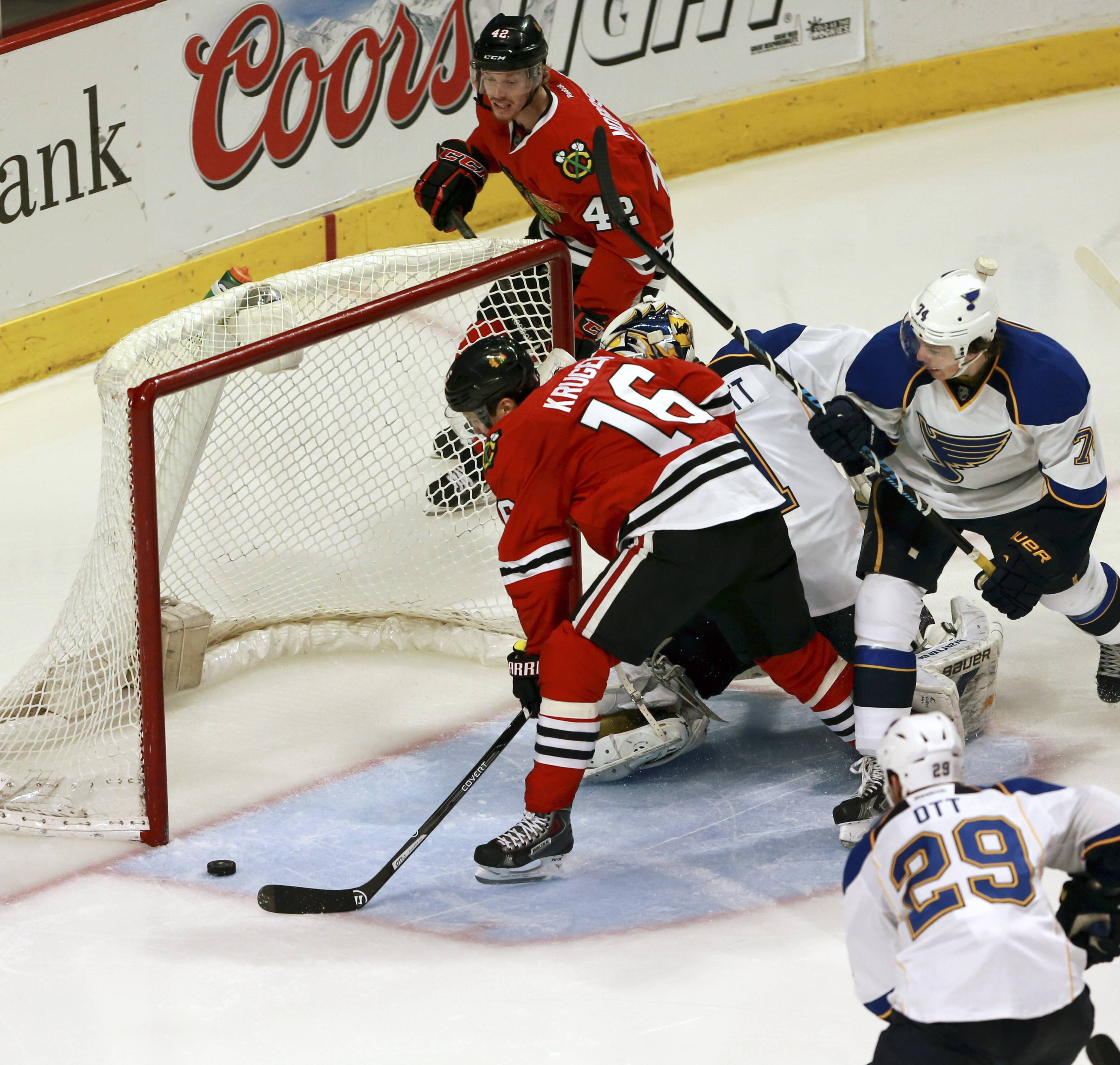 Blackhawks Marcus Kruger, left, scores against the St. Louis Blues in an NHL hockey game in Chicago on Sunday, April 6, 2014. The Blackhawks won 4-2.