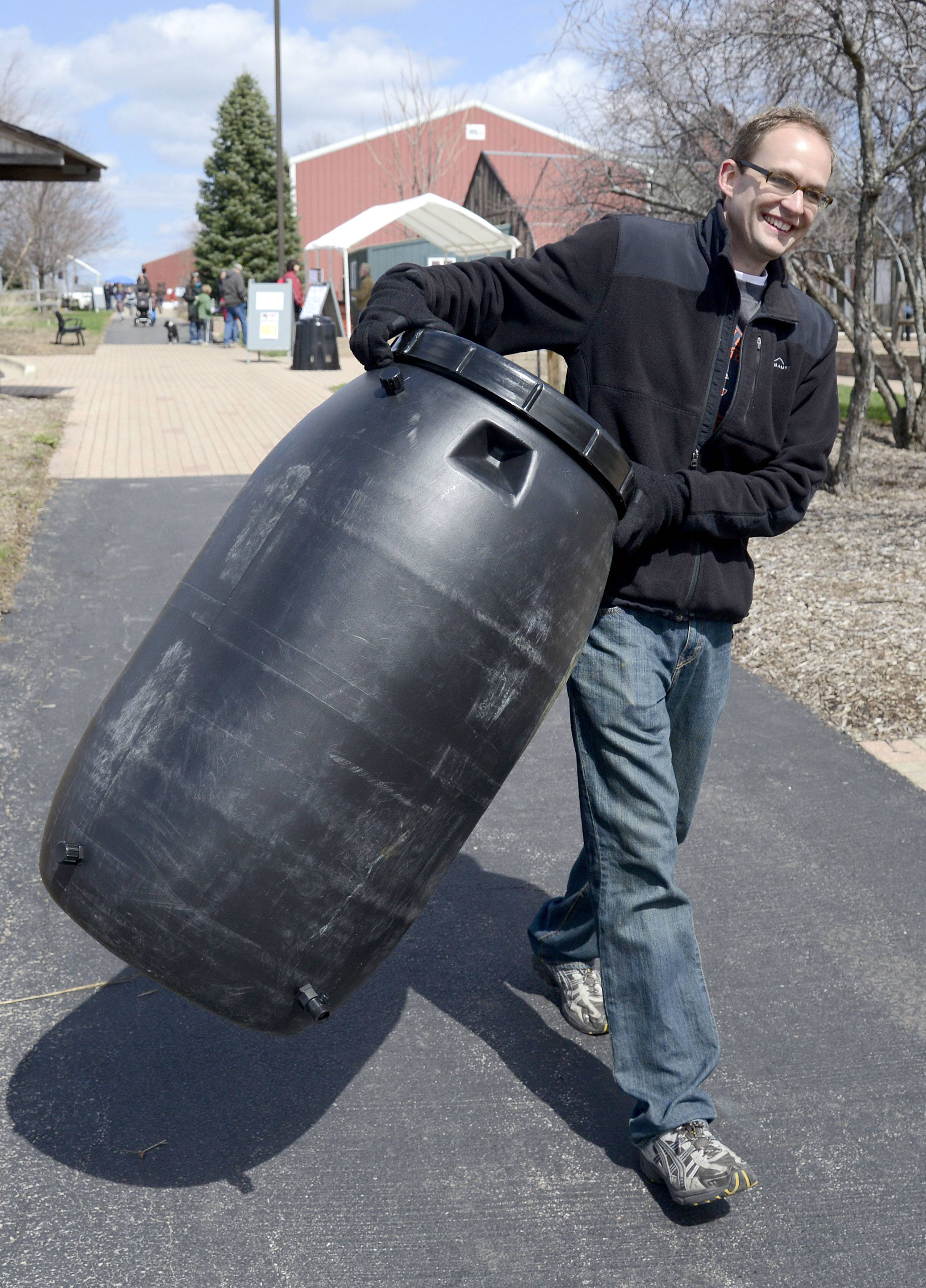 Nick Pohlman of Geneva lugs a rain barrel to his car after purchasing it at Peck Farm Park's Earth Day celebration last year.
