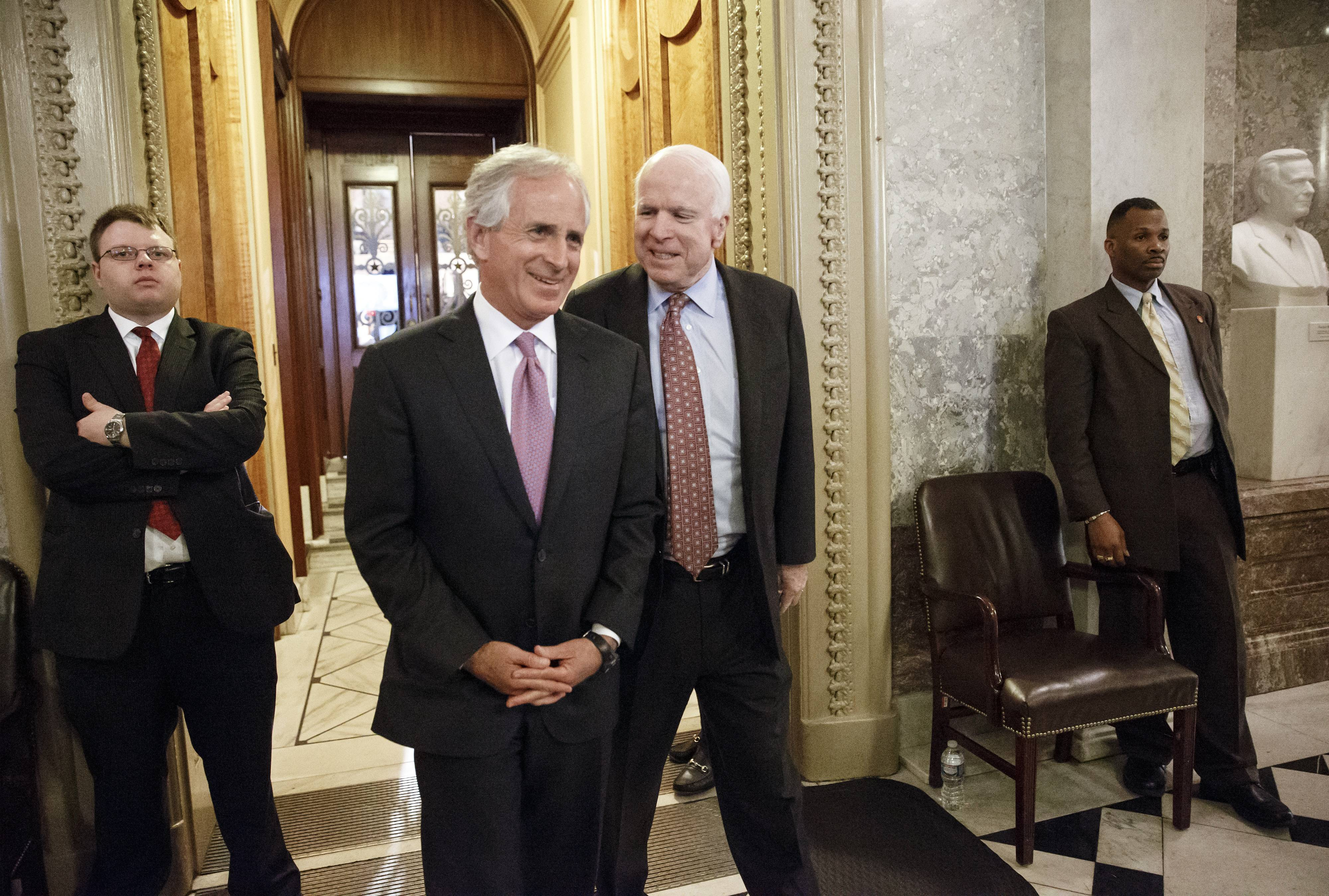 Sen. Bob Corker, R-Tenn., left, and Sen. John McCain, R-Ariz., join other lawmakers during the vote on restoring jobless benefits for the long-term unemployed, legislation that expired late last year, at the Capitol in Washington, Monday.