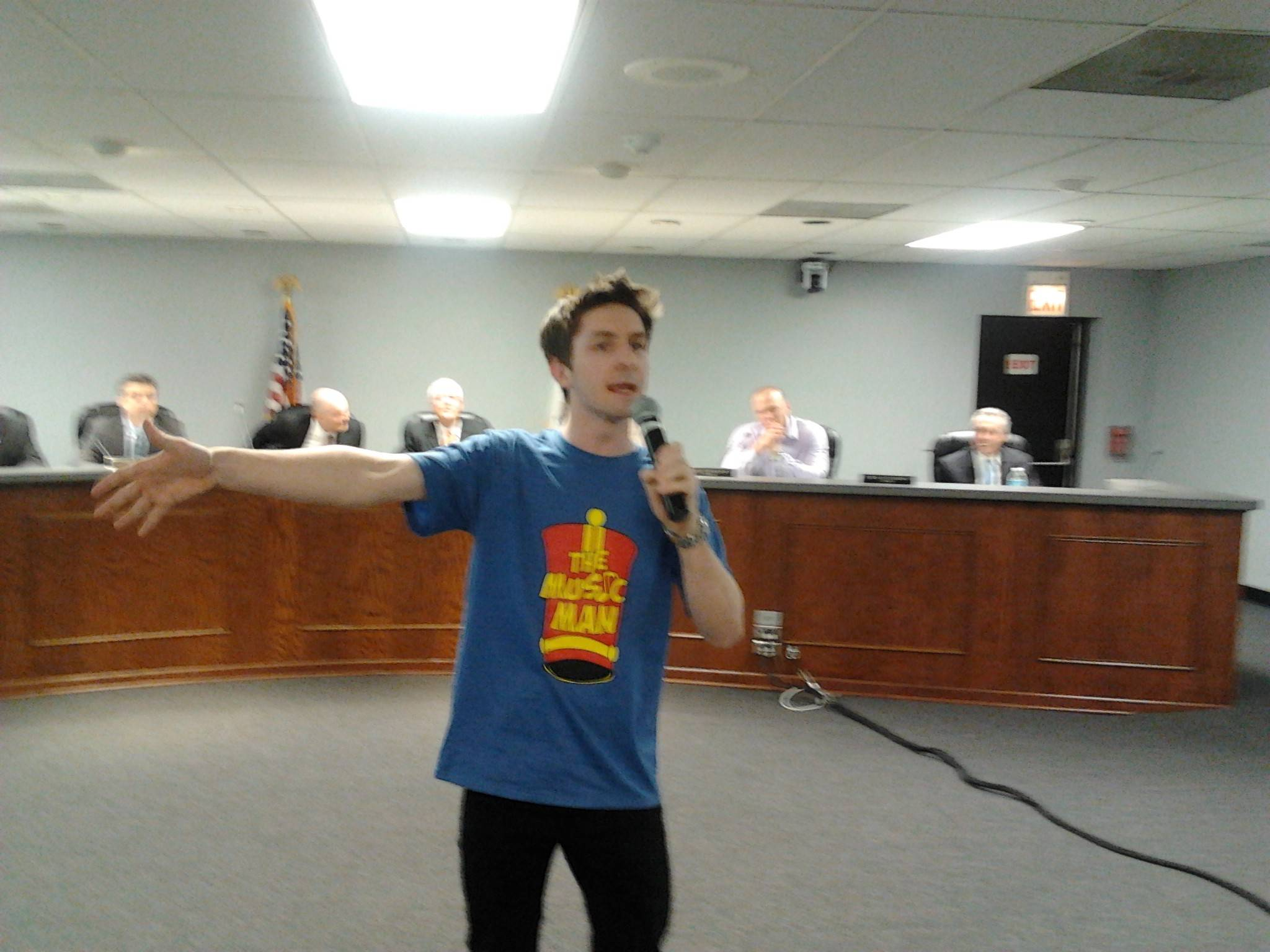 "Danny Euker, as lead character Harold Hill from ""The Music Man"" at Monday night's Lake Zurich village board meeting. Mayor Thomas Poynton helped arrange the surprise performance that featured 13 Lake Zurich High School students. Poynton said he wanted to help promote the play scheduled April 23-26."