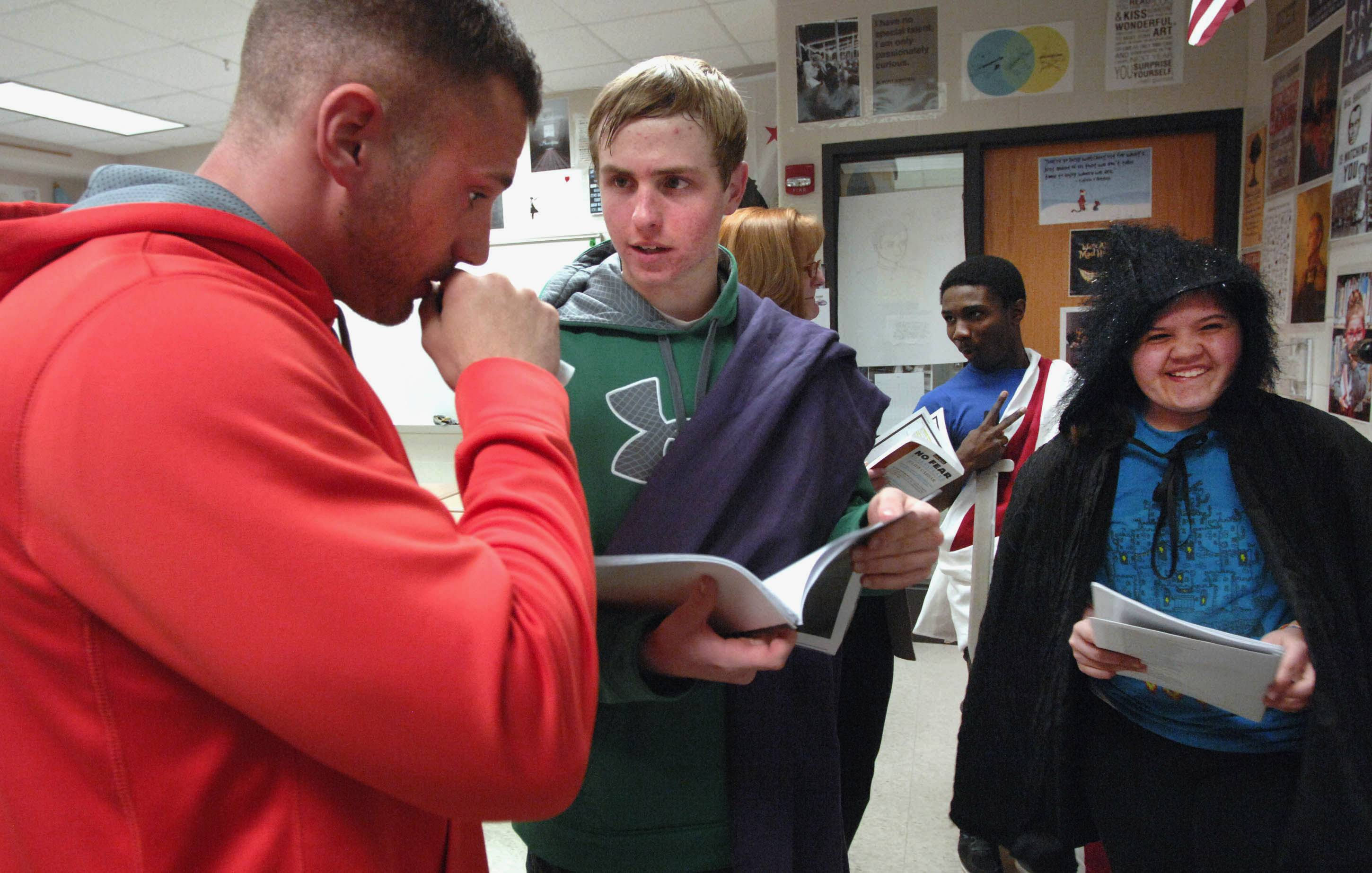 "English teacher Brad Bovenkerk, left, helps Jack Kestian, who plays Caesar, and Emily Henrichs, who plays a soothsayer, with their lines as students prepare to perform Shakespeare's ""Julius Caesar"" at Normal Community High School."