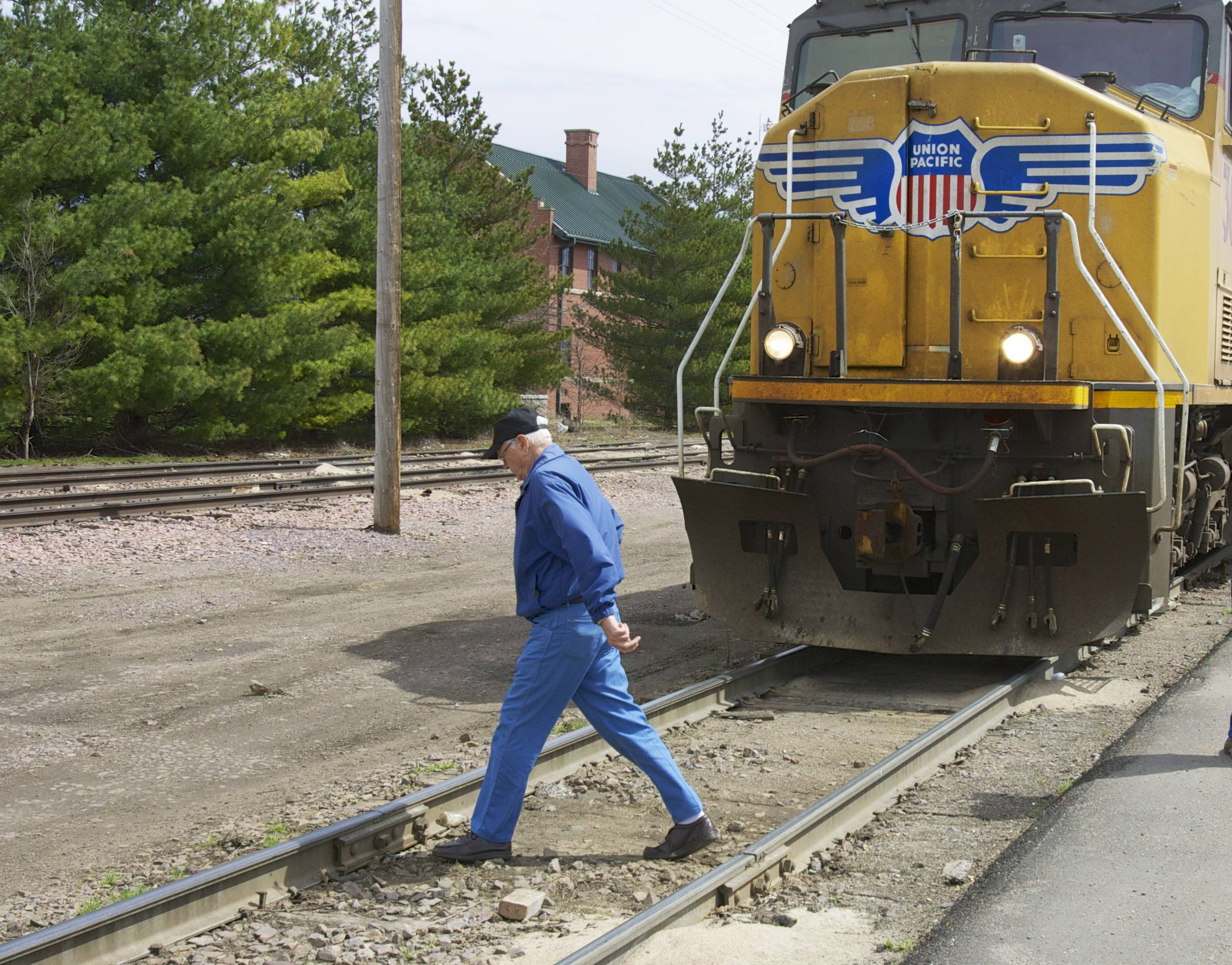 A man crosses a railroad track in front of a stationary locomotive in Fremont, Neb. Regulators and the railroad industry are launching a new campaign Tuesdayto educate people about the dangers of train tracks.