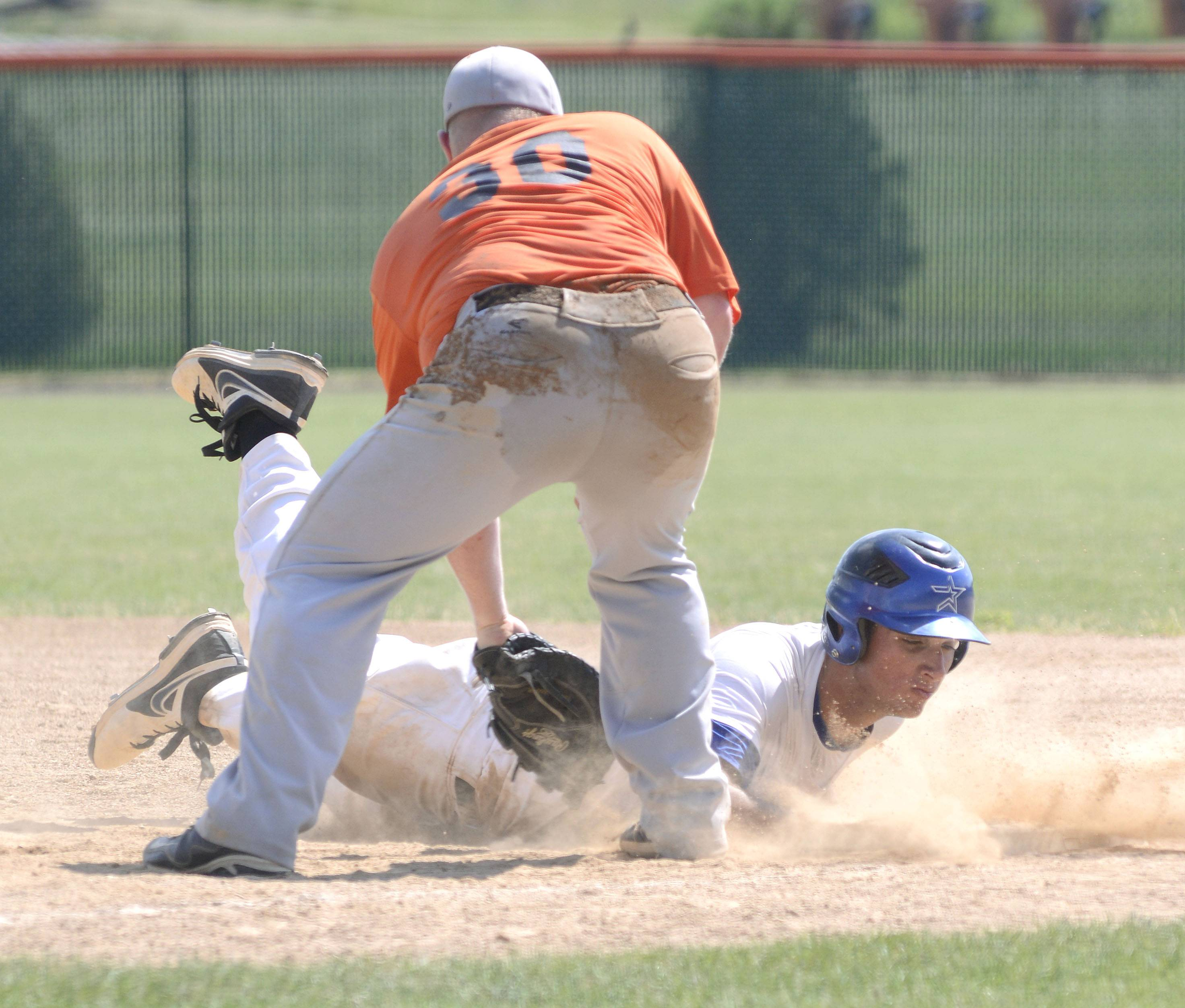St. Charles North's Joe Kuczek, pictured diving back into first base during a summer game against St. Charles East, was one of three North Stars to make the all-tournament team on their trip last week to Tennessee.