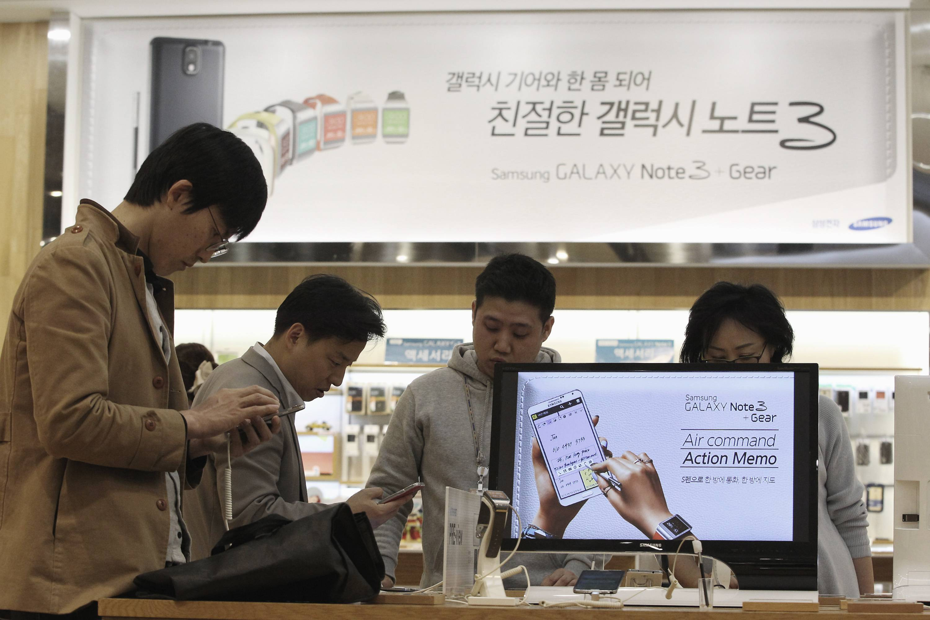 Visitors try out Samsung Electronics Co.'s Galaxy Note 3 at its showroom in Seoul, South Korea. Declining smartphone prices hit profit at Samsung for a second straight quarter.