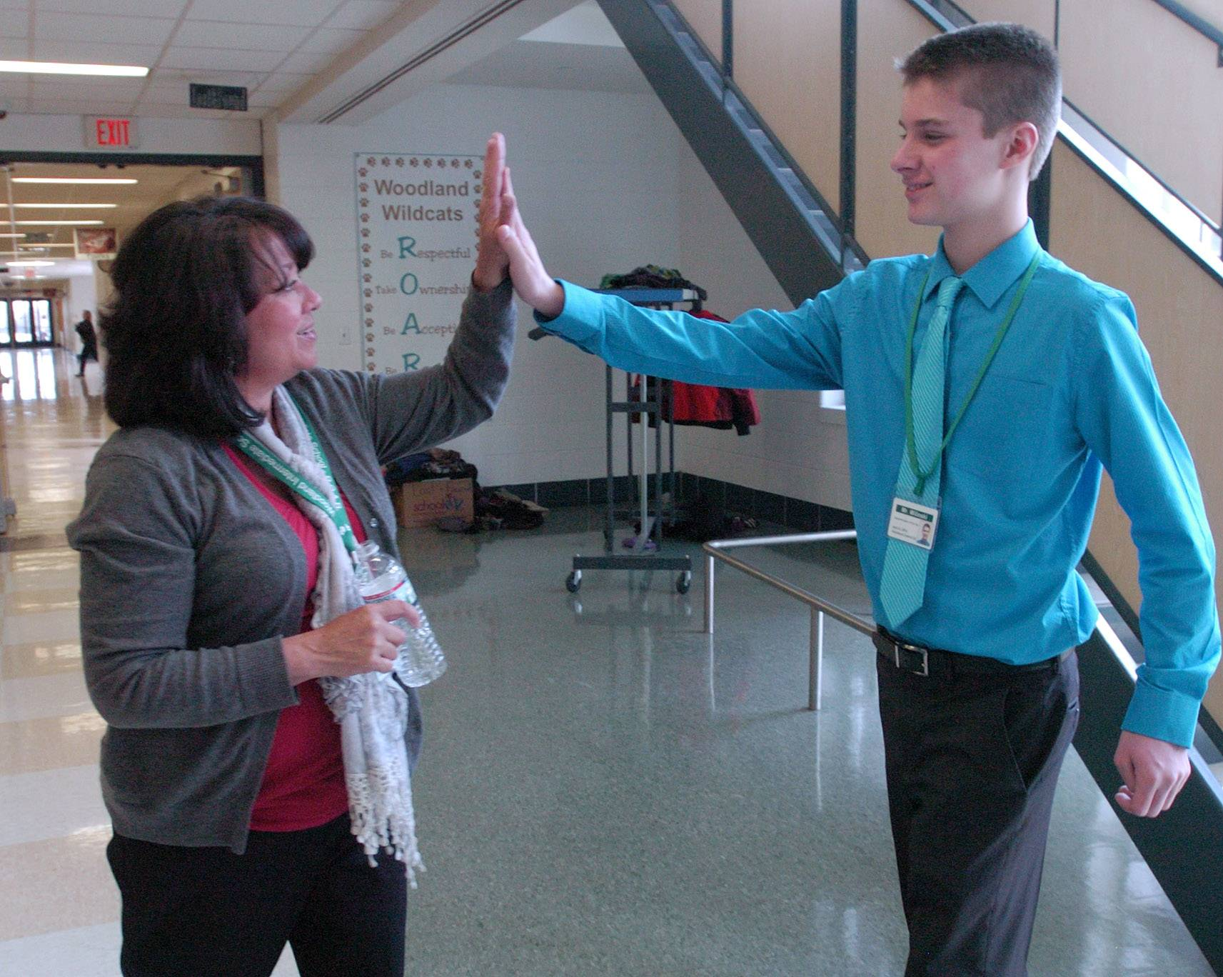 Woodland Intermediate School teacher Linda McCarthy high-fives Woodland Middle School seventh-grader Bradley Wilinski, who spent Tuesday as Superintendent for a Day. McCarthy was Wilinski's former art teacher in Gurnee-based Woodland Elementary District 50.