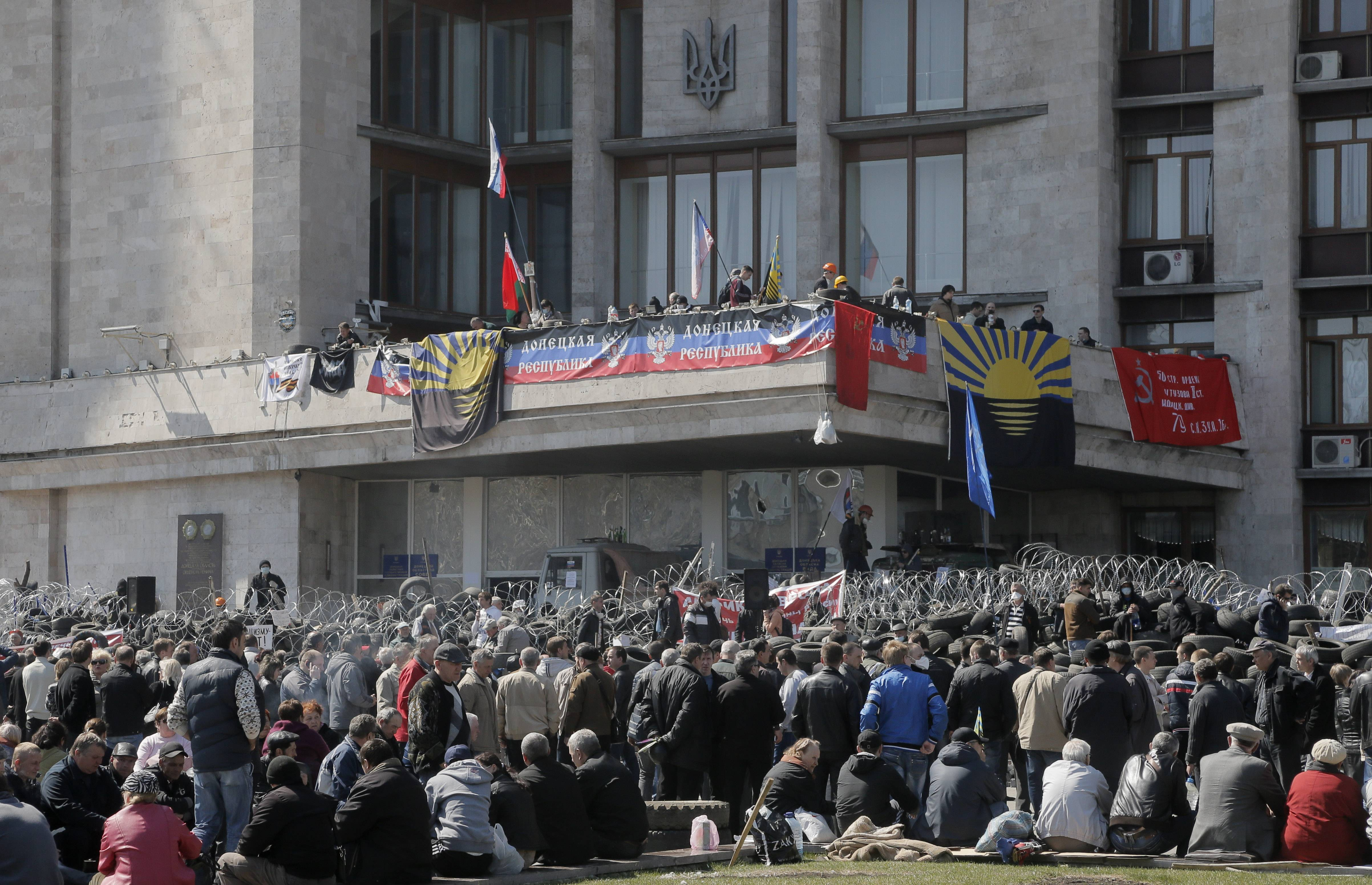 Pro-Russian activists stand at a barricade at the regional administration building in Donetsk, Ukraine, Tuesday, April 8, 2014.  In the city protesters dug in for their third day at the 11-story regional administration headquarters they captured on Sunday and began to declare their own parallel government. Ukrainian authorities on Tuesday reasserted control over an administration building in the country's second-largest city of Kharkiv, 250 Km ( 155 miles) north of Donetsk, which had been seized by pro-Russian protesters, and authorities detained some dozens.