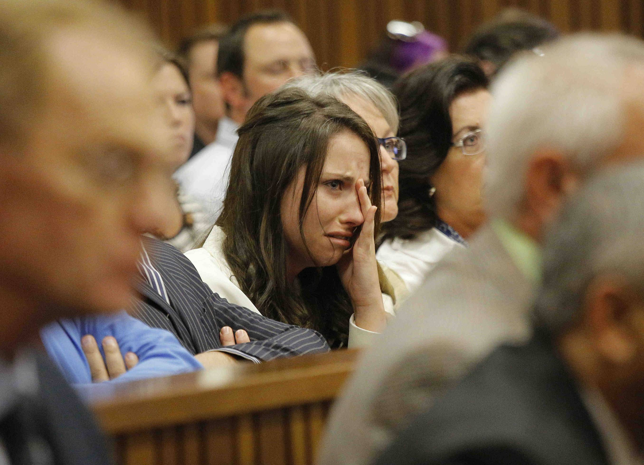 Sister of Oscar Pistorius, Aimee Pistorius, center, cries as she listens as her brother testifies in court in Pretoria, South Africa, Tuesday. Pistorius is charged with the murder of his girlfriend Reeva Steenkamp, on Valentines Day 2013.