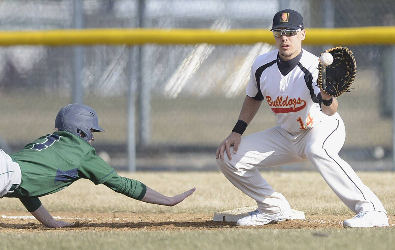 Batavia's Bartlett's Mike Wick slides back safely to first base a fraction of a second before the ball hits the hit of Batavia's Micah Coffey in the third inning on Tuesday, April 8.