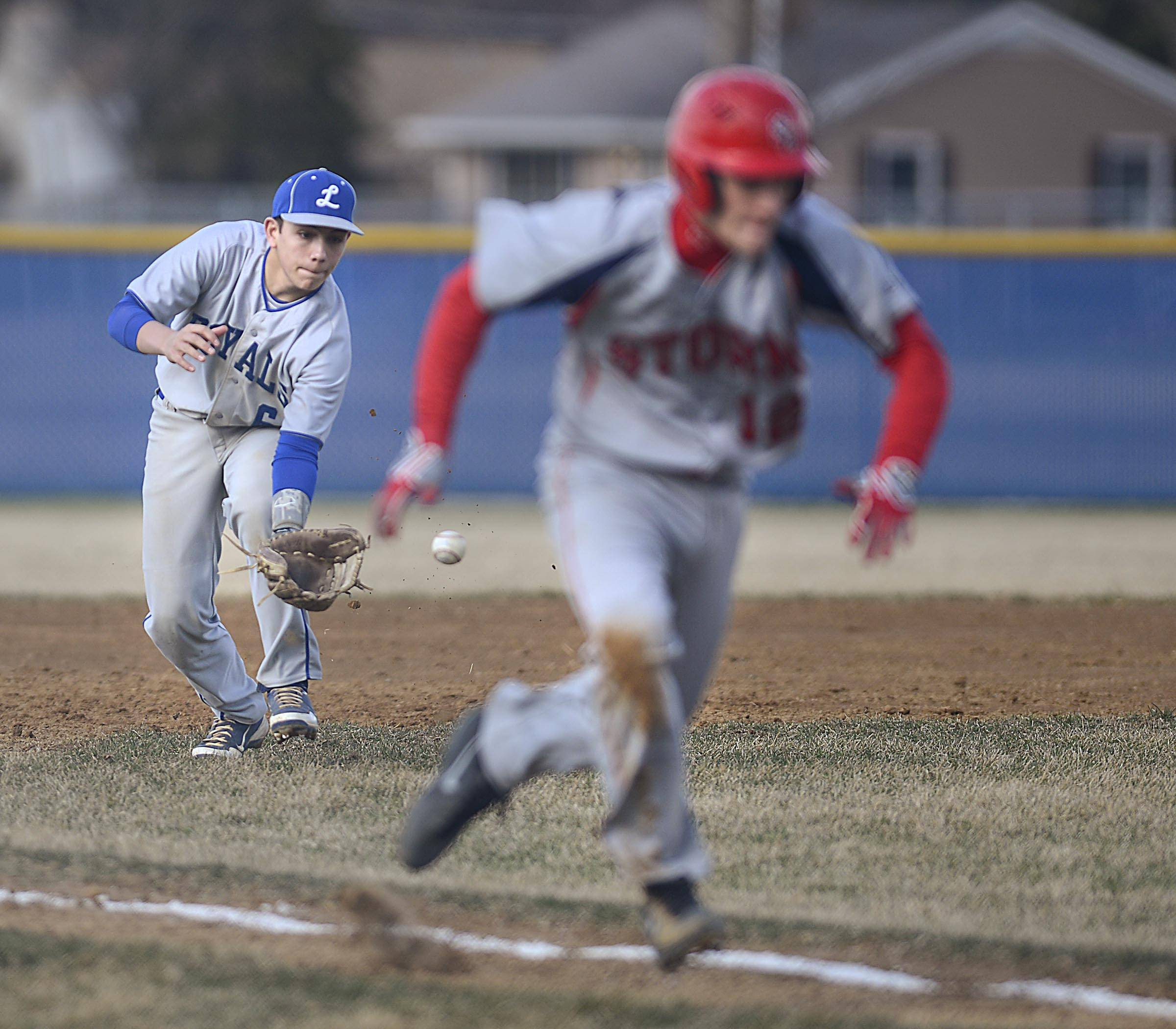 Larkin third baseman Dan Lenz fields a ground ball as  South Elgin's Kyle Hays scores from third on the hit by teammate Zach Filippo in the first inning Tuesday in Elgin.