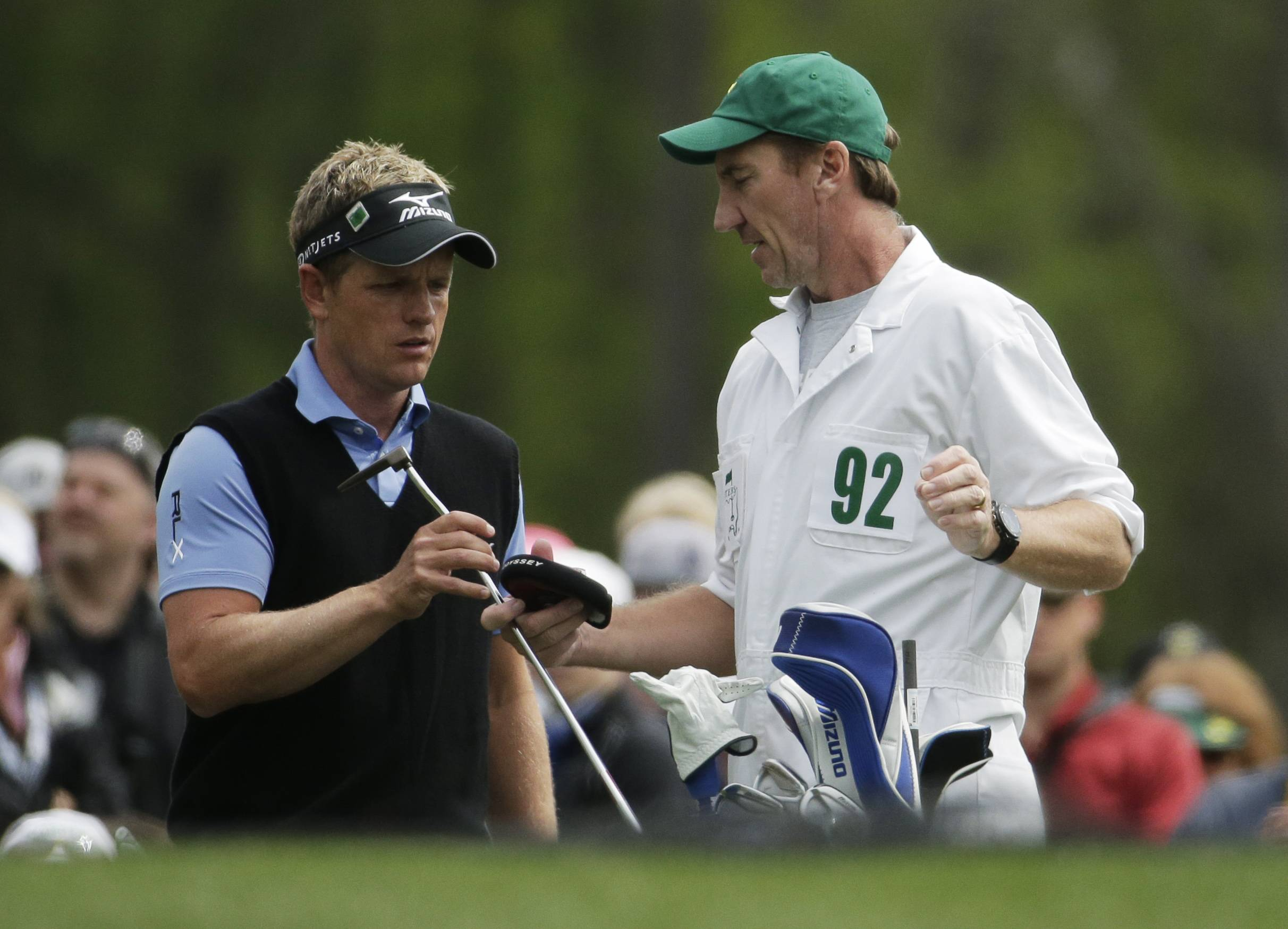Luke Donald, of England, gets a club from his caddie on the 12th green during a practice round for the Masters golf tournament Tuesday, April 8, 2014, in Augusta, Ga.