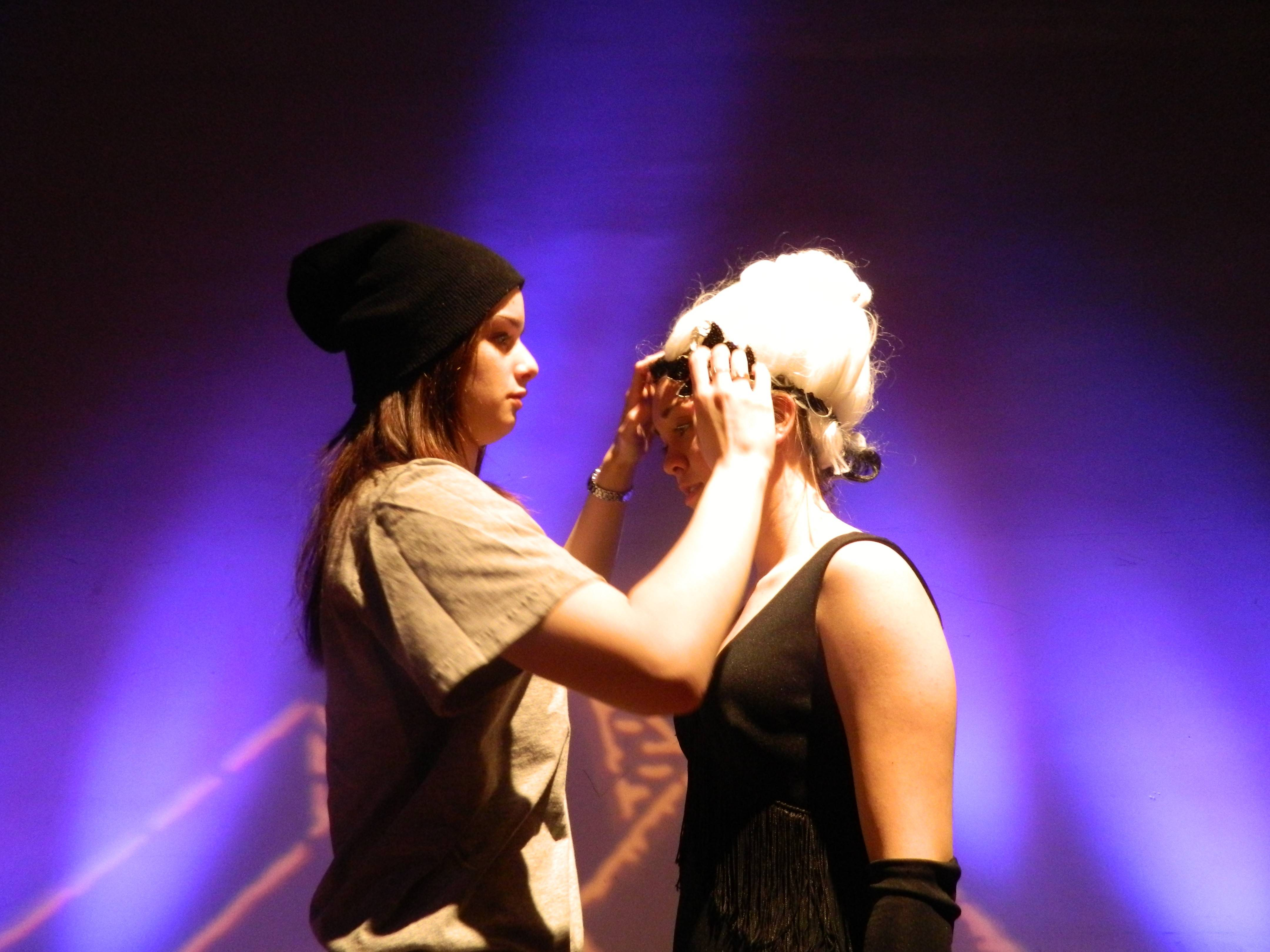 "Stefani Lah, assistant director, helps Elizabeth Clary put on her Mrs. Potiphar wig at a dress rehearsal for the musical ""Joseph"" at Buffalo Grove High School."