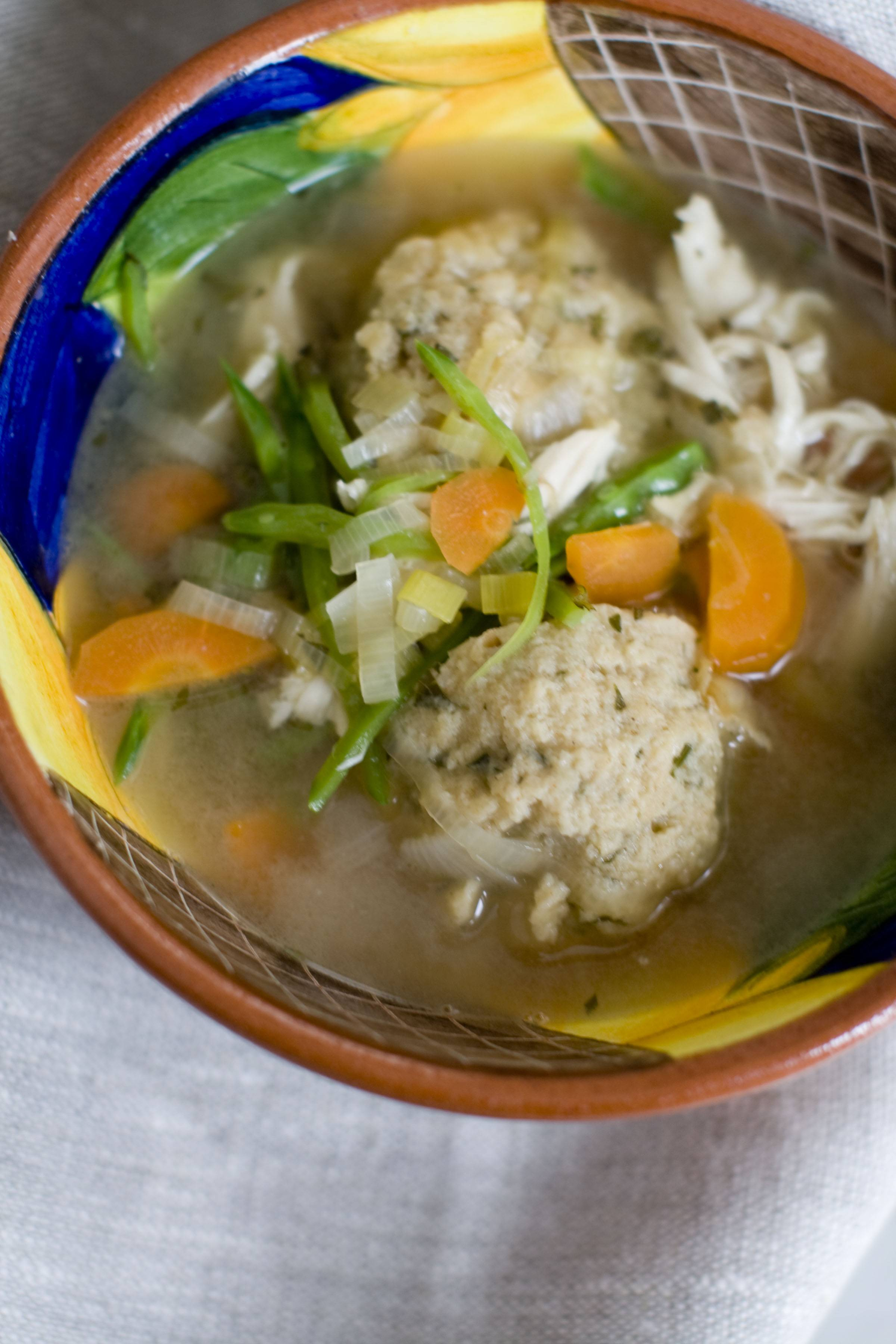 Spring vegetables give matzo ball soup a fresh, seasonal taste.