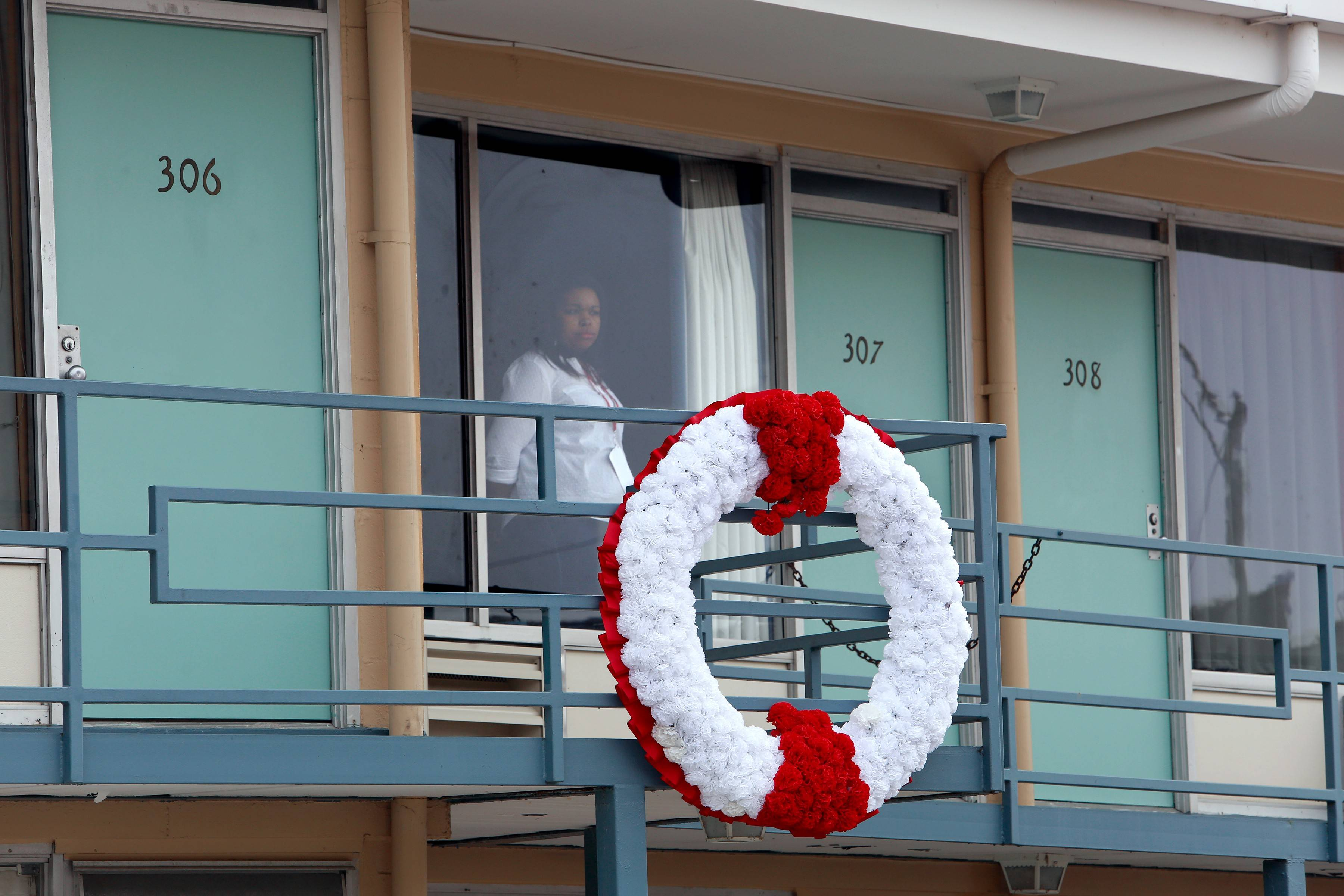 A woman watches the crowd during the grand reopening of the National Civil Rights Museum in Memphis, Tenn., Saturday, April 5. The balcony, outside Room 306 at the Lorraine Motel, is the site where Dr. Martin Luther King Jr. was assassinated on April 4, 1968.