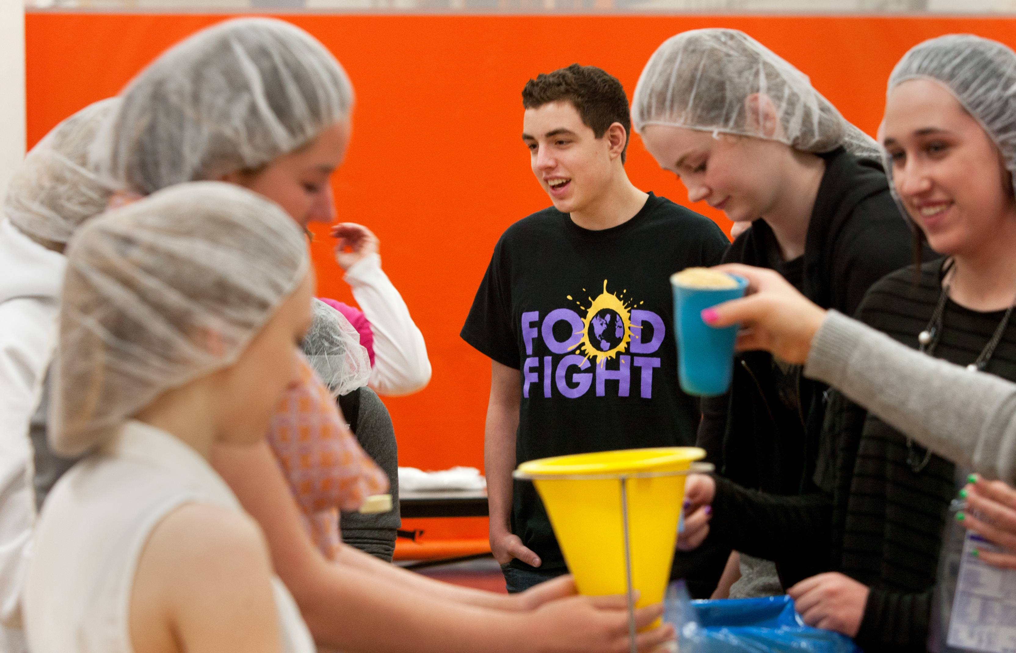 Naperville North High School students pack high-protein meals Wednesday during the sixth annual student-led Food Fight event. Naperville Central junior Jared Prosapio, center, is leading student organizers in this year's effort to pack 158,000 meals for starving people in other countries.