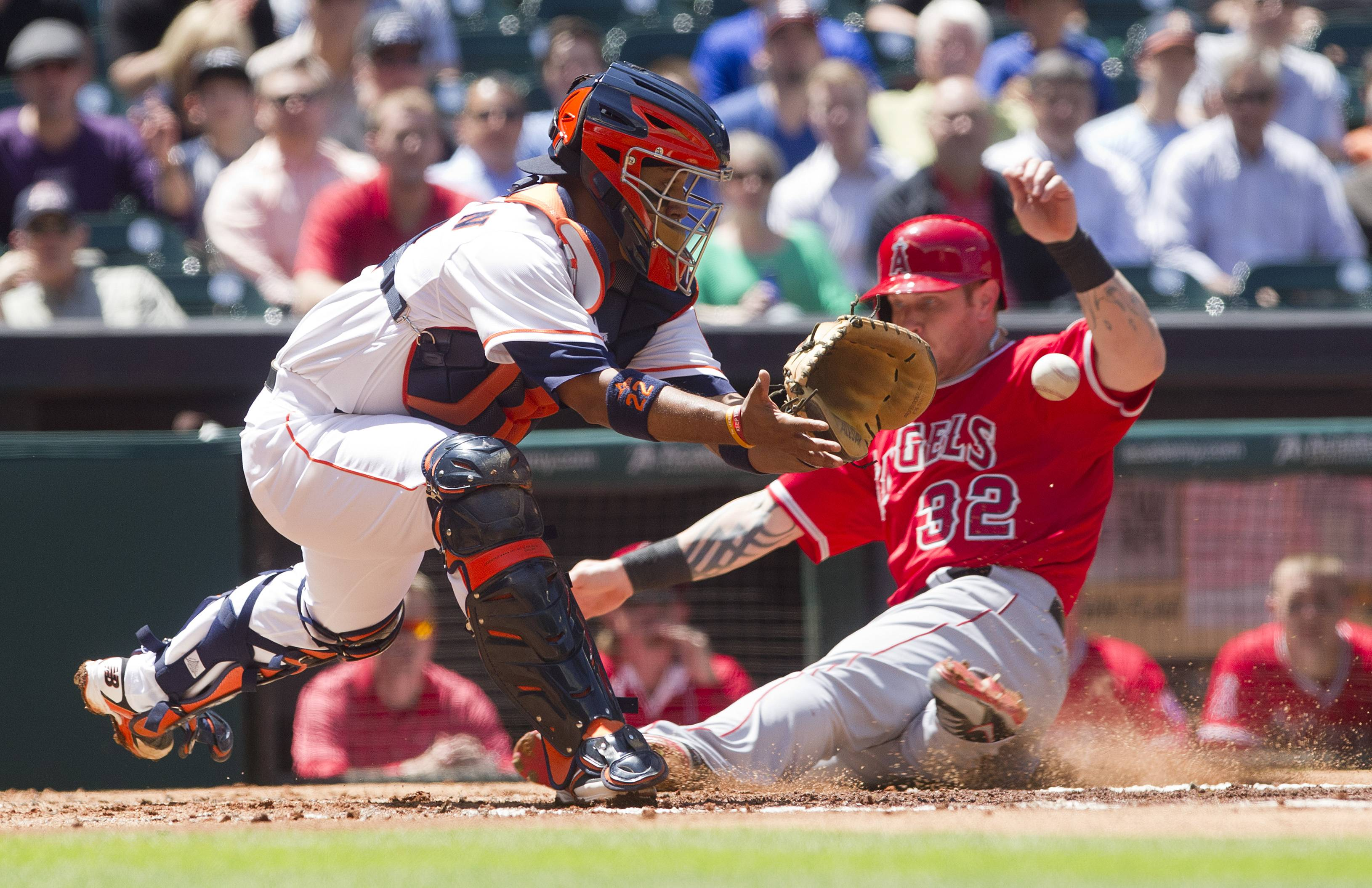 Los Angeles Angels' Josh Hamilton (32) beats the throw to Houston Astros catcher Carlos Corporan (22) for score during the first inning during a MLB America League baseball game Monday, April 7, 2014, in Houston. The Los Angeles Angels defeated the Houston Astros 9-1. (AP Photo/ The Courier, Jason Fochtman)
