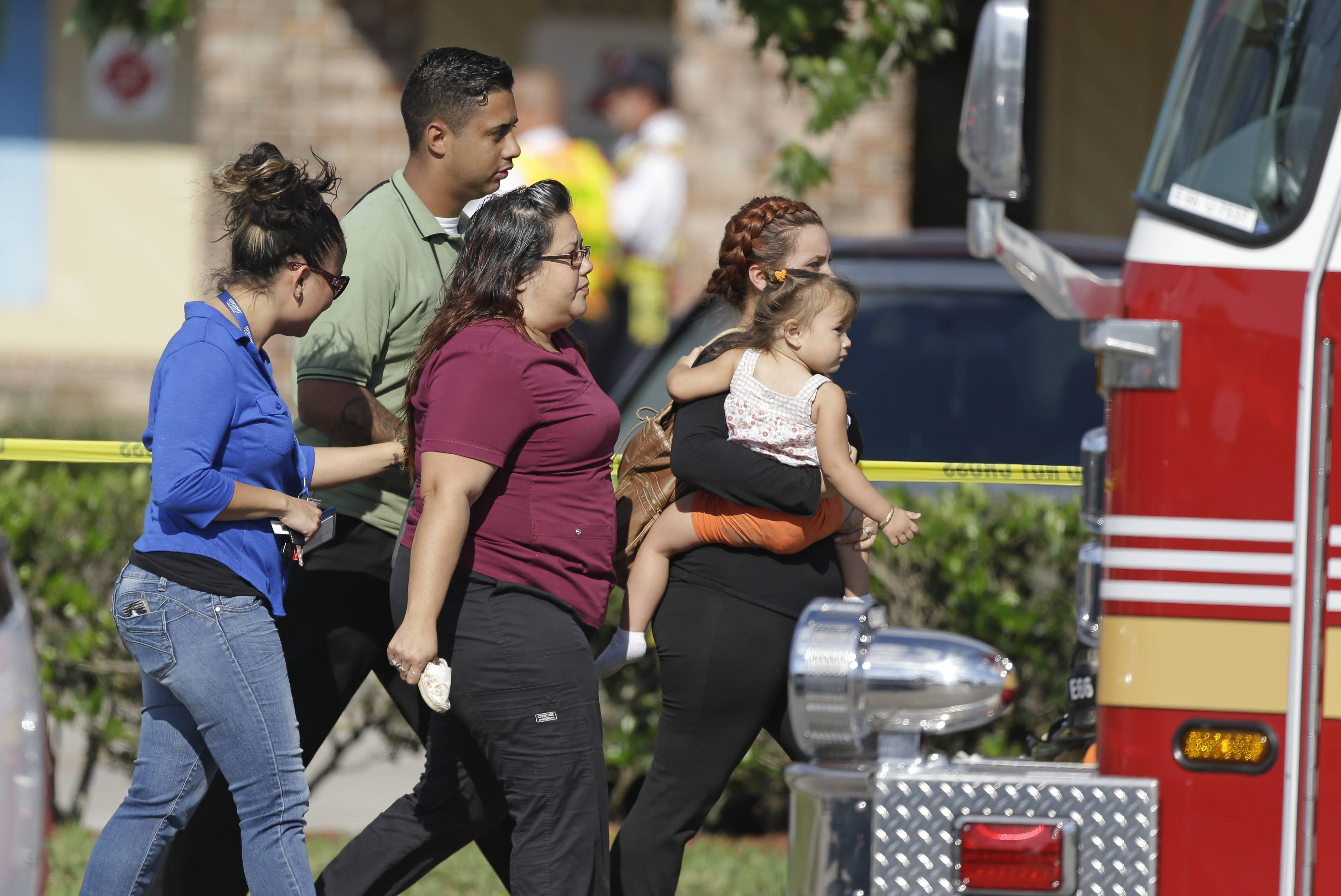 Parents and relatives leave a day care center with their children after a vehicle crashed into the center Wednesday in Winter Park, Fla. One child was killed and at least 14 other people were injured.