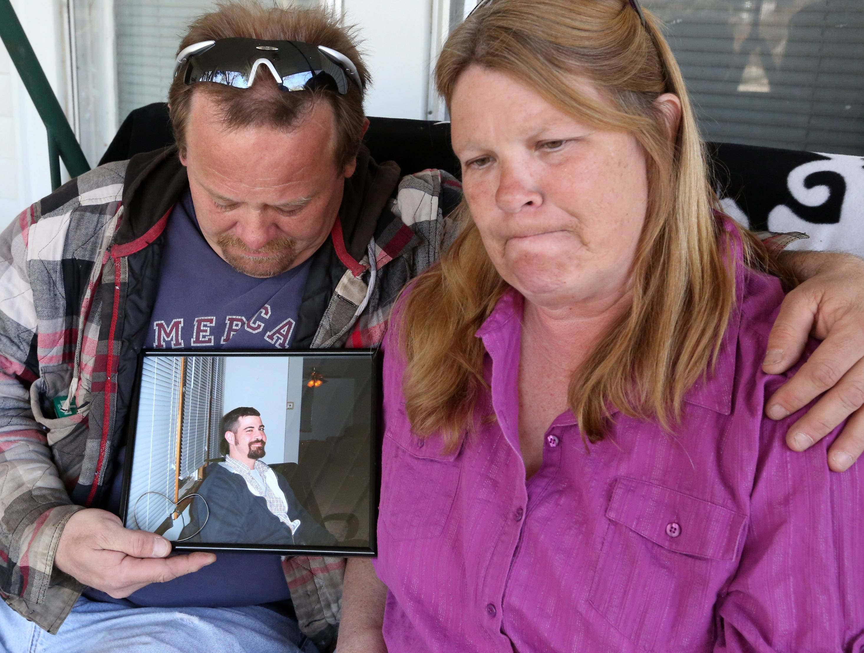 Jamie and Liz Schramm, on their porch in Wauconda, holding a photograph of John T. Nightingale, as they talk about their friend. Nightingale was shot to death by Wauconda police Monday after he refused to drop a handgun, authorities said.