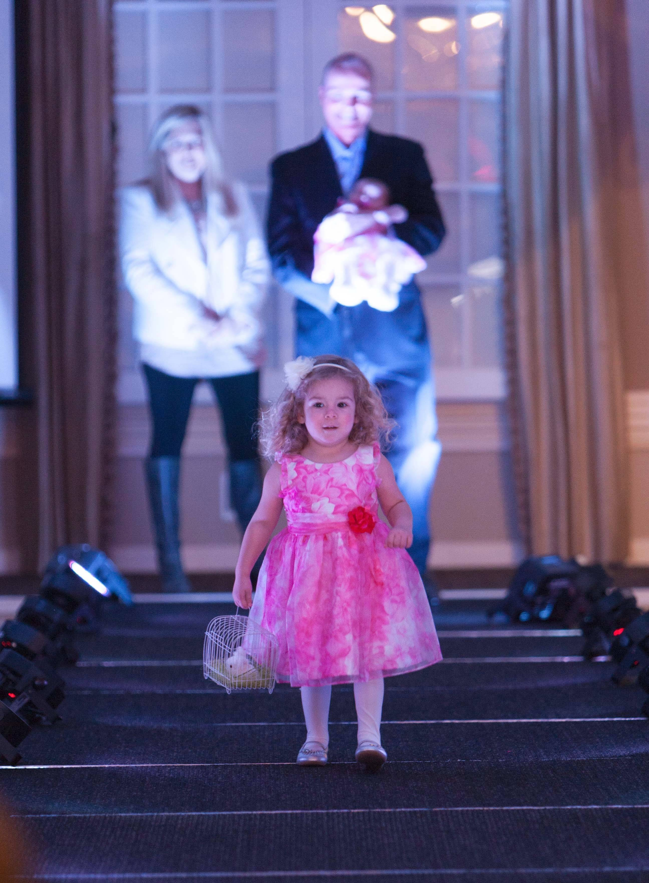 Chloe Cornell, 3, walks the runway at St. Mary's Services' fundraiser fashion show as parents Chris and Jennie Cornell of Gurnee look on. Chris is holding St. Mary's newest adoptee, 2-month-old Kate.
