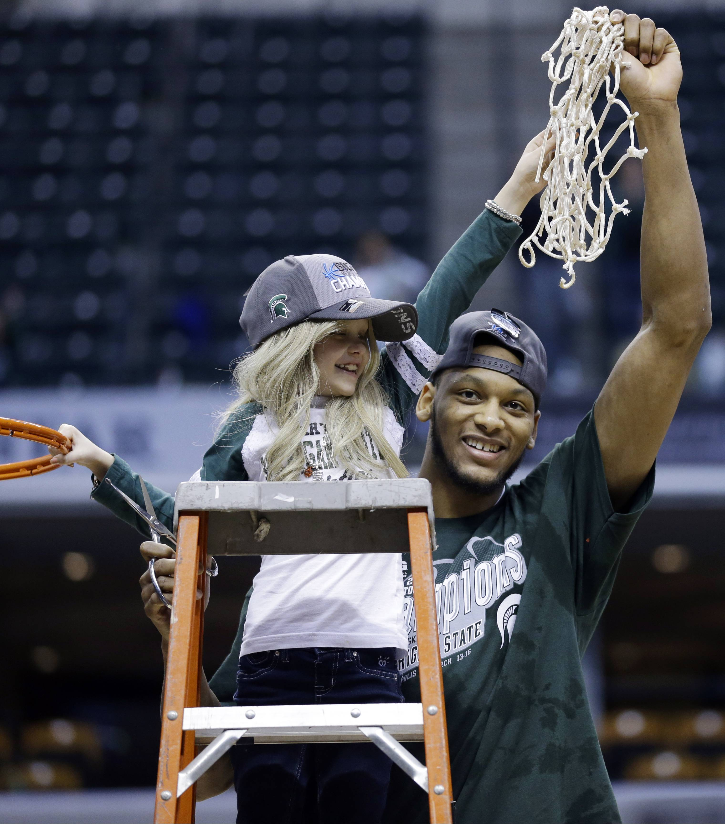 "Michigan State forward Adreian Payne, right, hoists the net with Lacey Holsworth, who was battling cancer, after Michigan State defeated Michigan 69-55 in an NCAA college basketball game in the championship of the Big Ten Conference tournament in Indianapolis. The 8-year-old girl died at her St. Johns, Mich., home late Tuesday ""with her mommy and daddy holding her in their arms."""