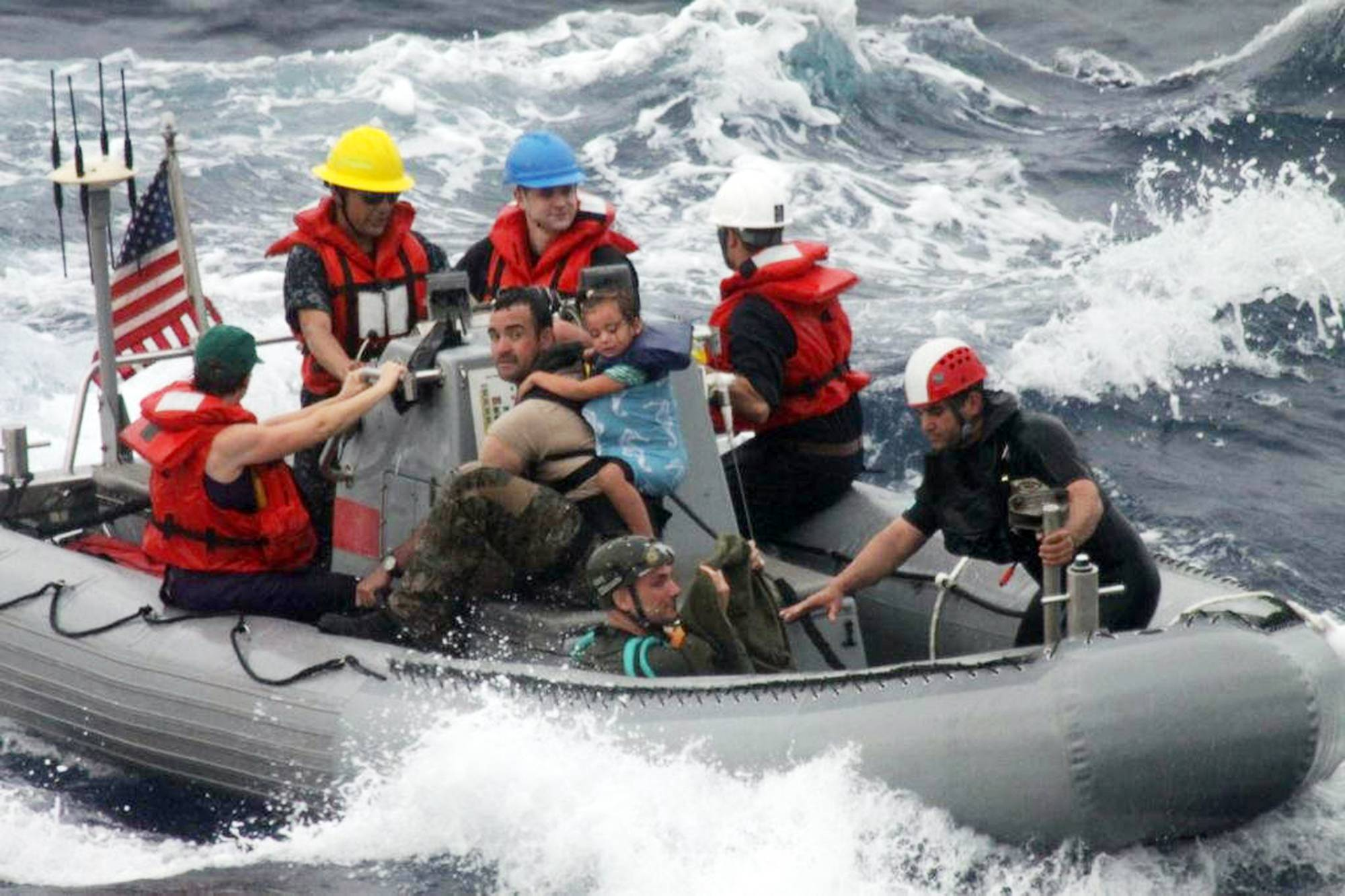 Sailors from the frigate USS Vandegrift assist in the rescue of the Kaufman family with a sick infant on the ship's small boat, as part of a joint U.S. Navy, Coast Guard and California Air National Guard rescue effort.