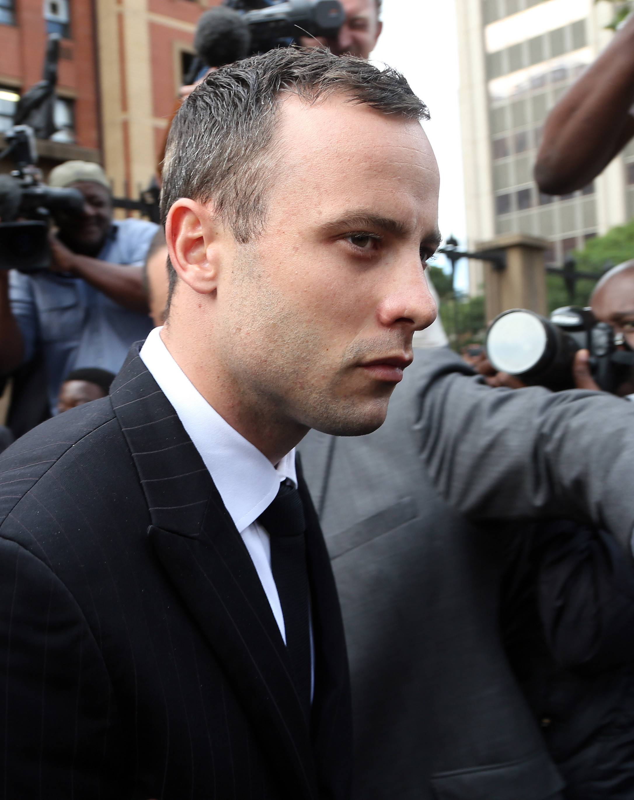 Oscar Pistorius leaves the high court in Pretoria, South Africa, Wednesday. He is charged with murder for shooting dead his girlfriend, Reeva Steenkamp, on Valentine's Day in 2013.