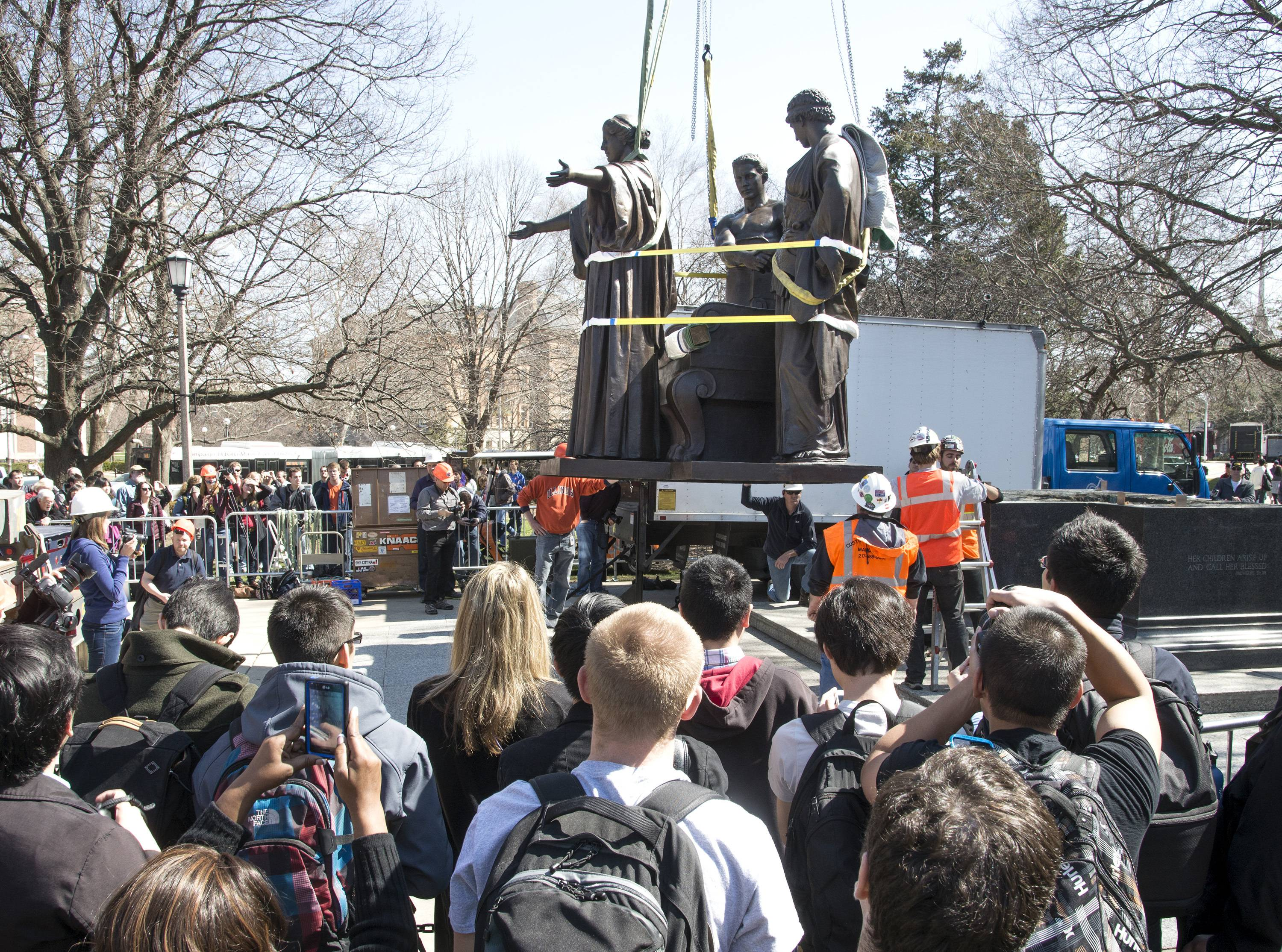 A crowd watches as the Alma Mater is reinstalled Wednesday in front of Altgeld Hall at the University of Illinois in Urbana.