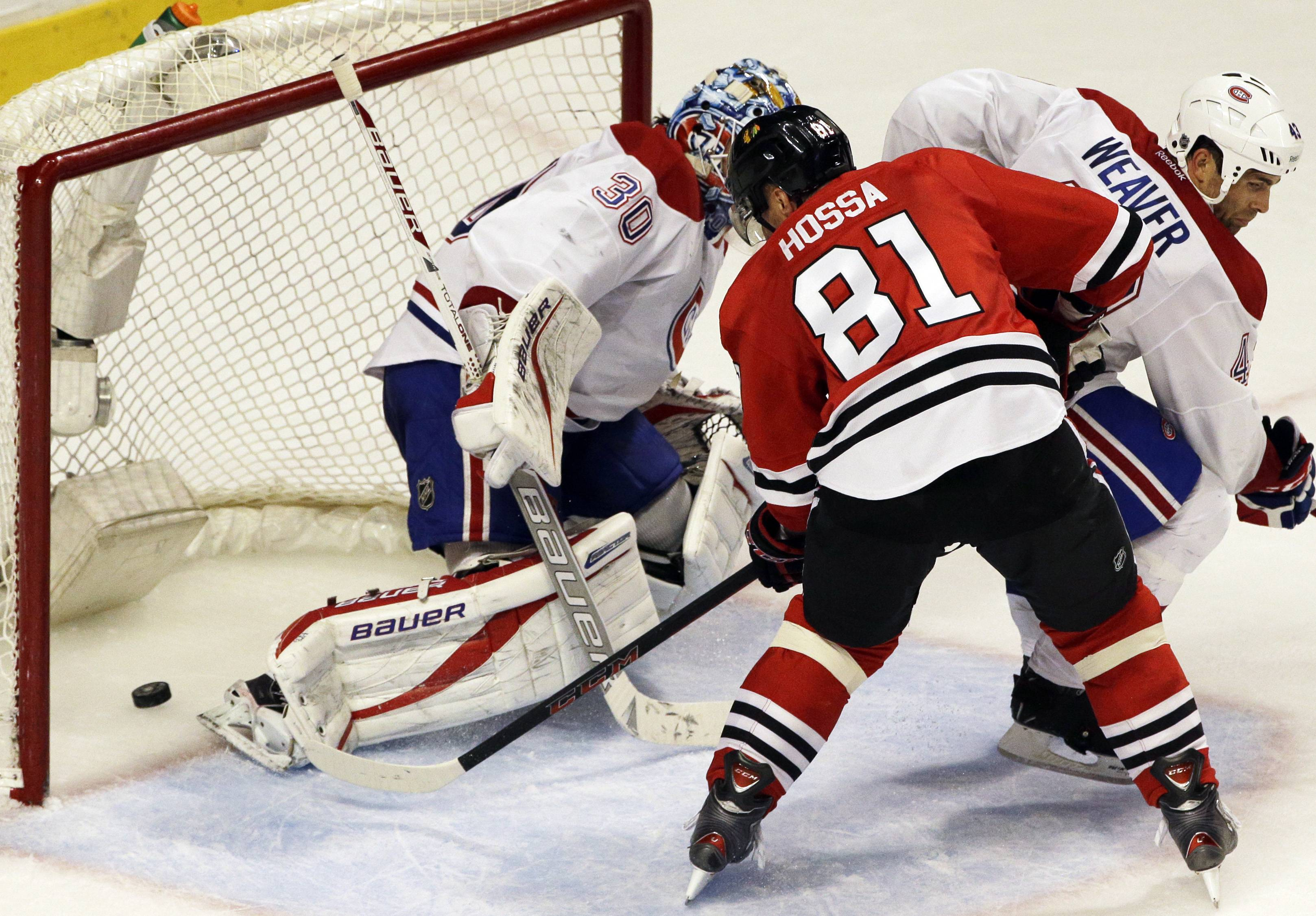 The Blackhawks' Marian Hossa scores against Canadiens goalie Peter Budaj during the final minute to send the game to overtime.