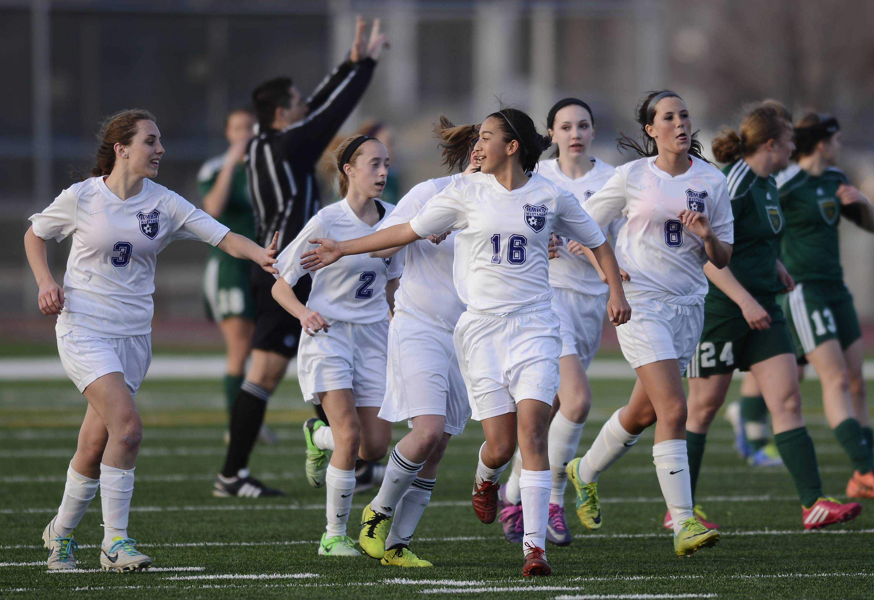 Rolling Meadows' Mary Collins, left, celebrates her first-half goal with teammates including Natalie D'Souza (16) during Wednesday's home game with Fremd.