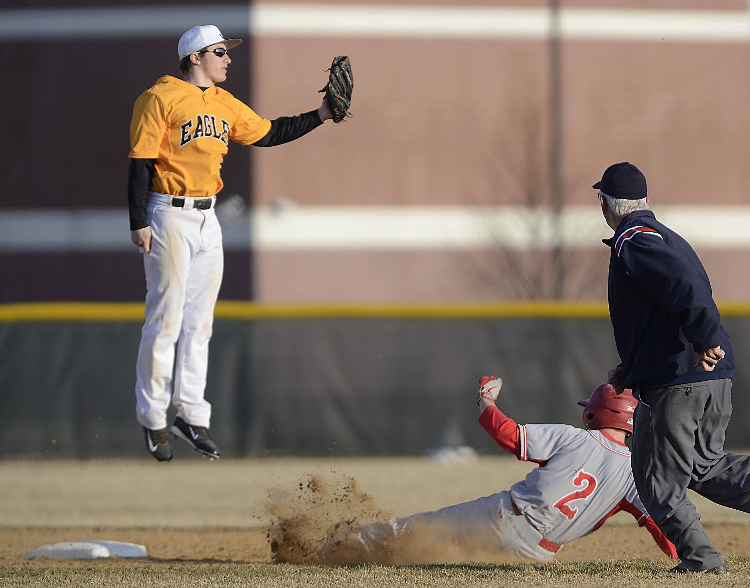 Barrington's Nick Caminiti slides safely into second base as the throw goes past Jacobs second baseman Grant Kale Wednesday in Algonquin.