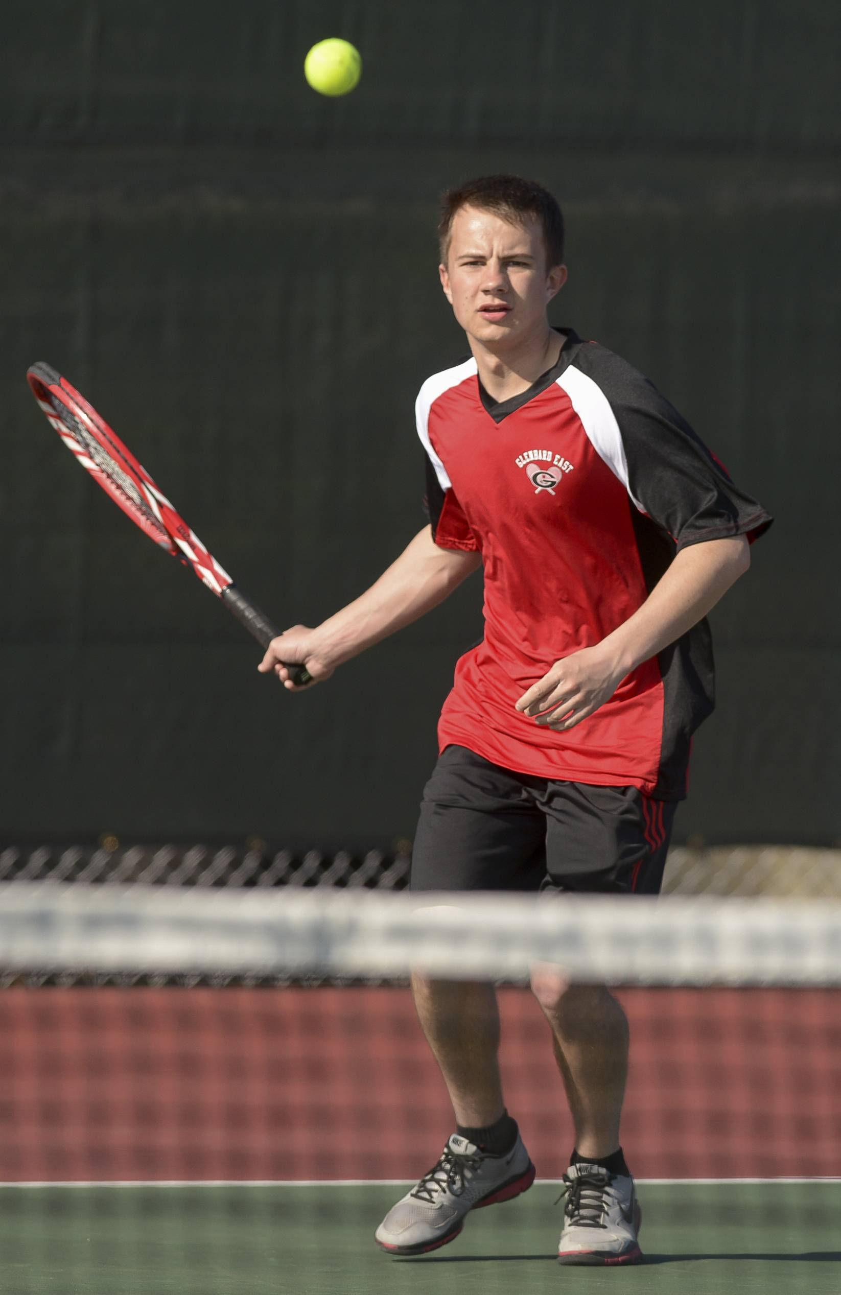 Glenbard East's Krystian Nowloka keeps an eye on the ball during a match against Montini's Brian Konopacz during boys varsity tennis in Lombard.
