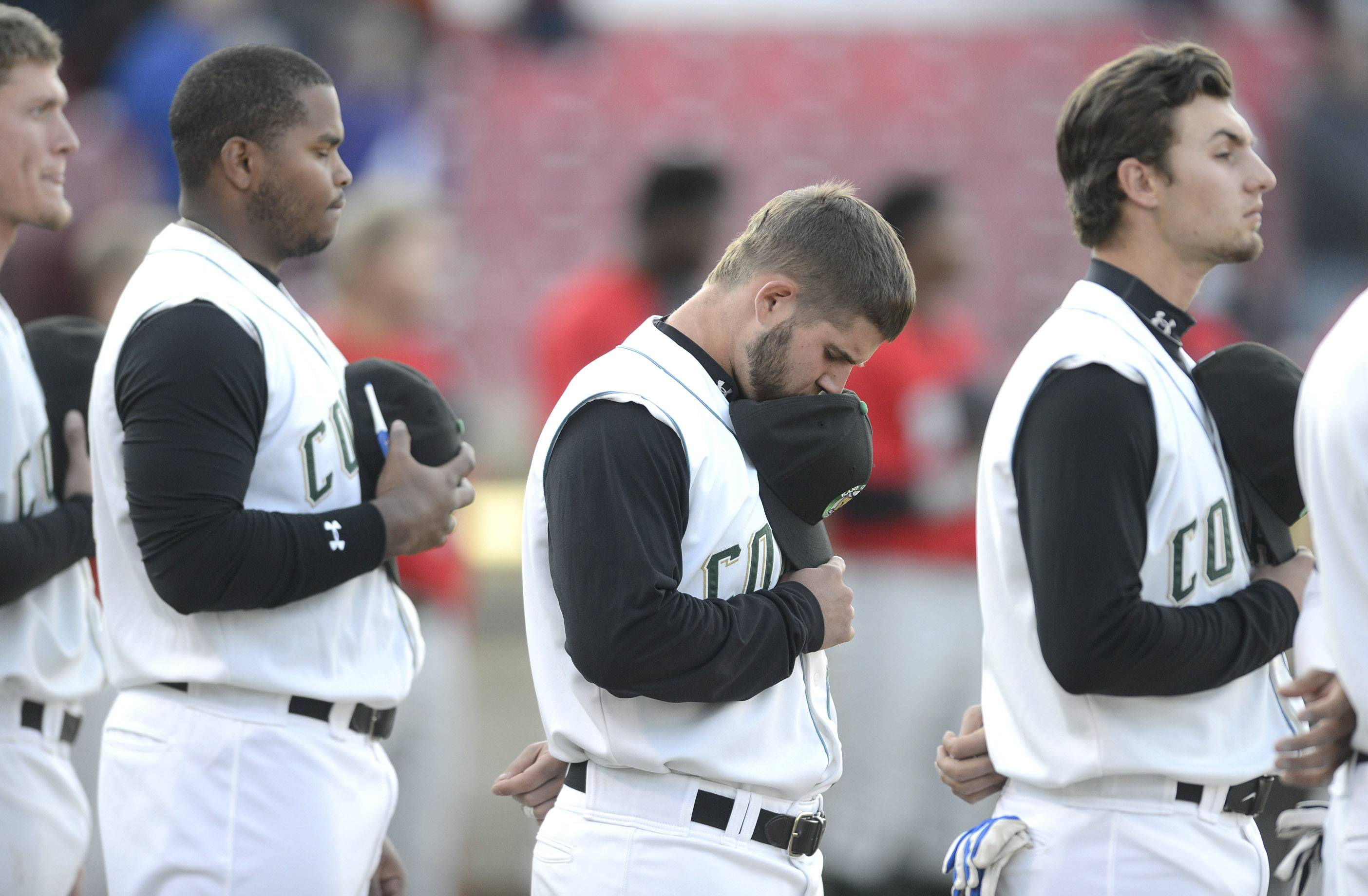 Kane County Cougars third baseman Ben Carhart bows his head as the National Anthem is played.