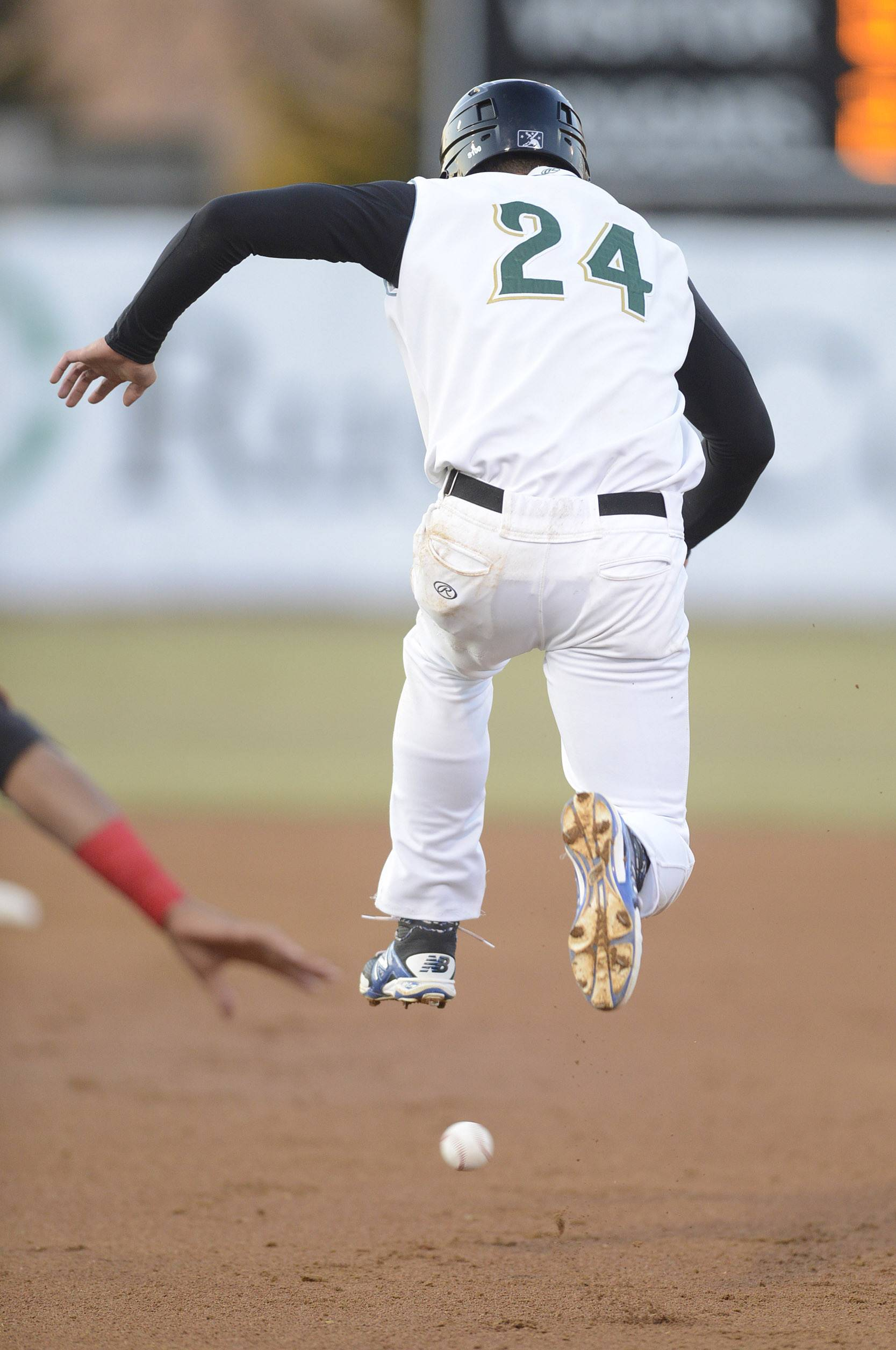 Jacob Rogers of the Kane County Cougars leaps over a ball as he heads to second base in the first inning.