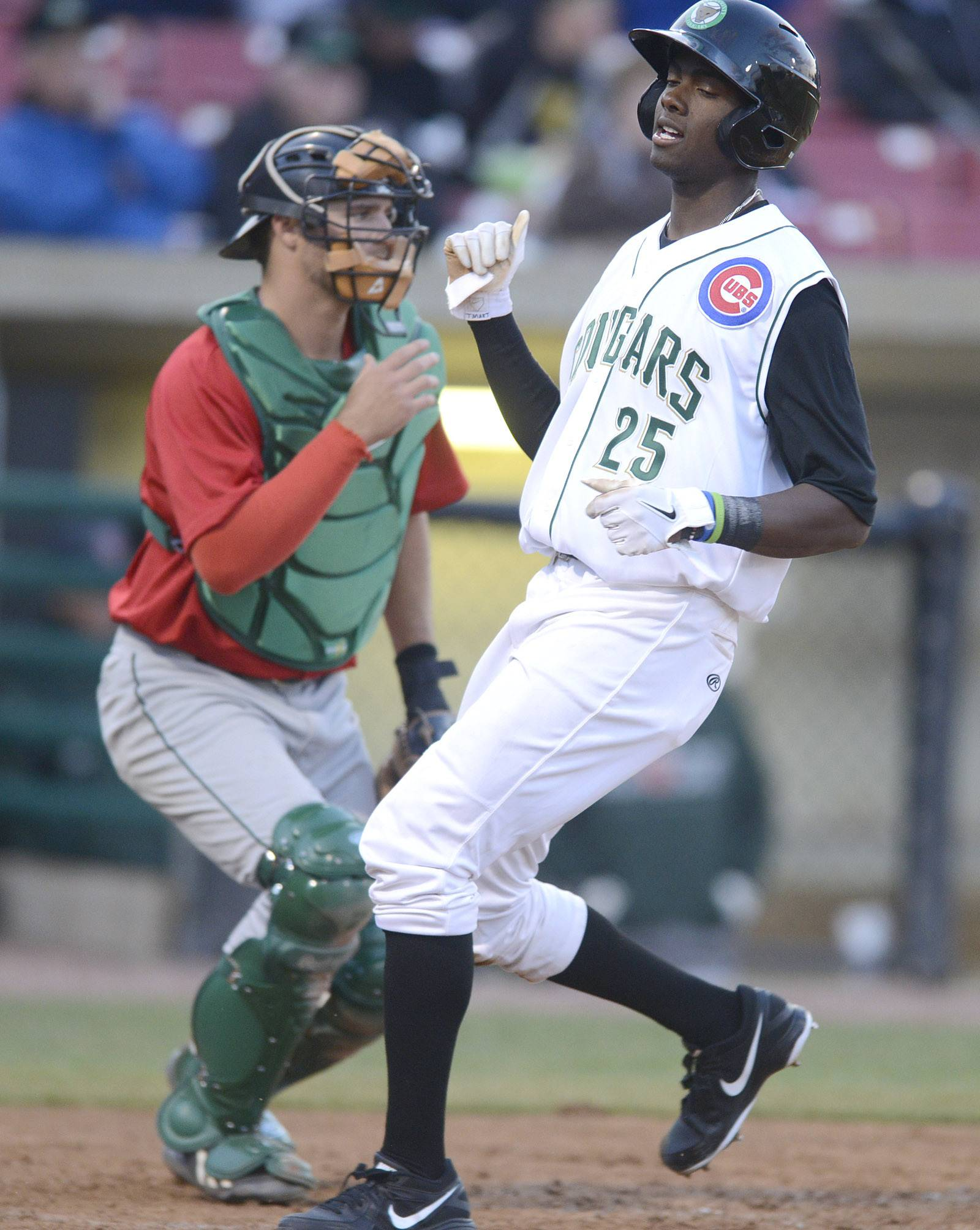 Kane County Cougars' Trey Martin trots past Fort Wayne TinCaps catcher Ryan Miller and touches home plate to score in the second inning.