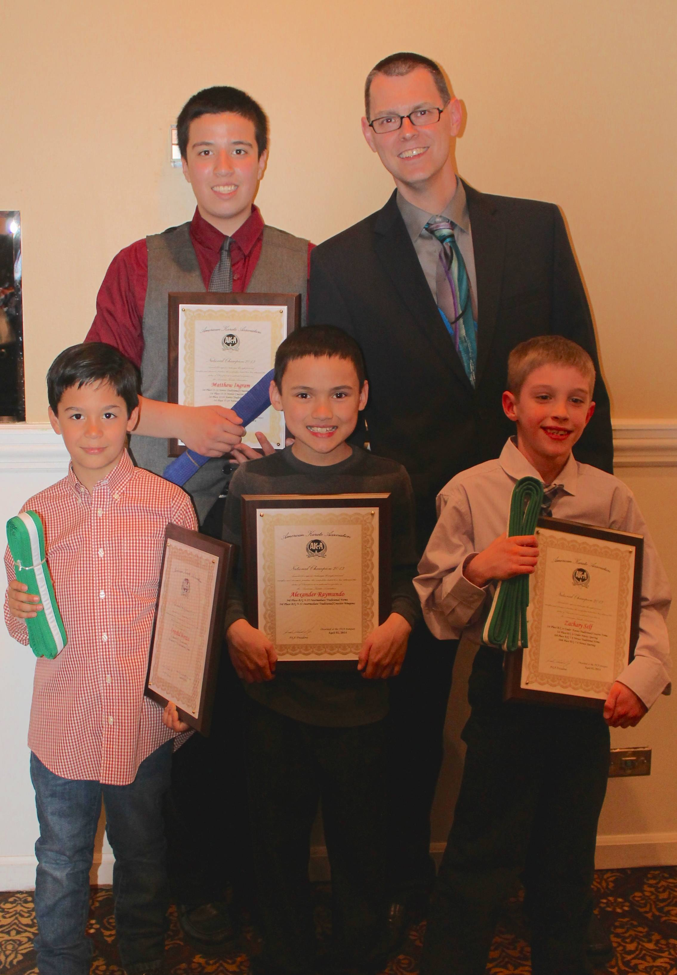 The Baekwoon Mu Sul Tigers show the national awards earned during the 2013 tournament season. Back row (l-r): Matthew Ingram, Sensei Jeremy Talbott. Front row (l-r): Cristobal Morales, Alex Raymundo, and Zachary SelfKathy Raymundo