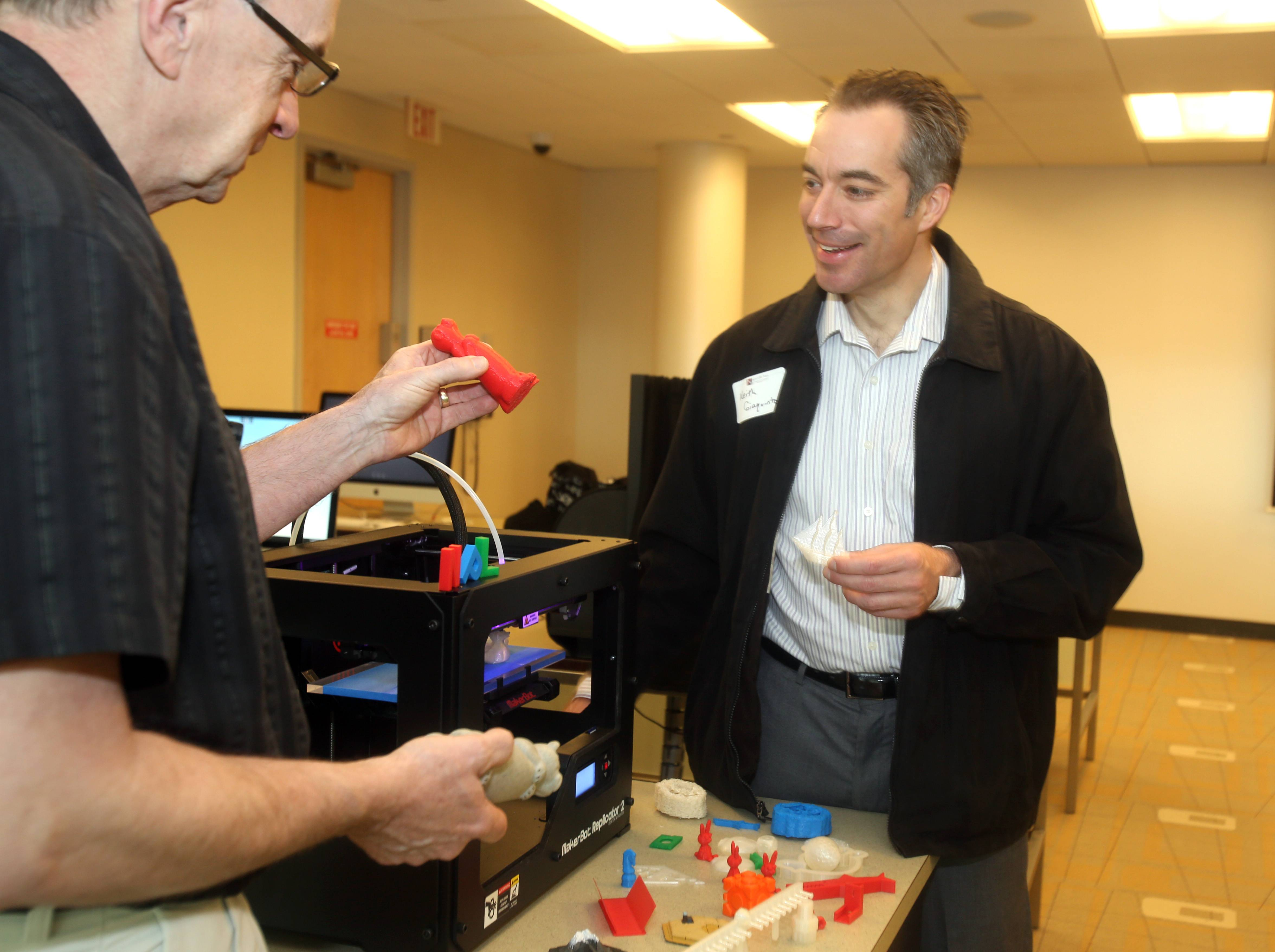 Naperville Public Library help desk employee Jeff Smallwood explains the new 3-D printer in the Idea Lab at the 95th Street Library to chiropractor Keith Giaquinto, who toured the new lab Thursday morning with other members of the Naperville Area Chamber of Commerce.