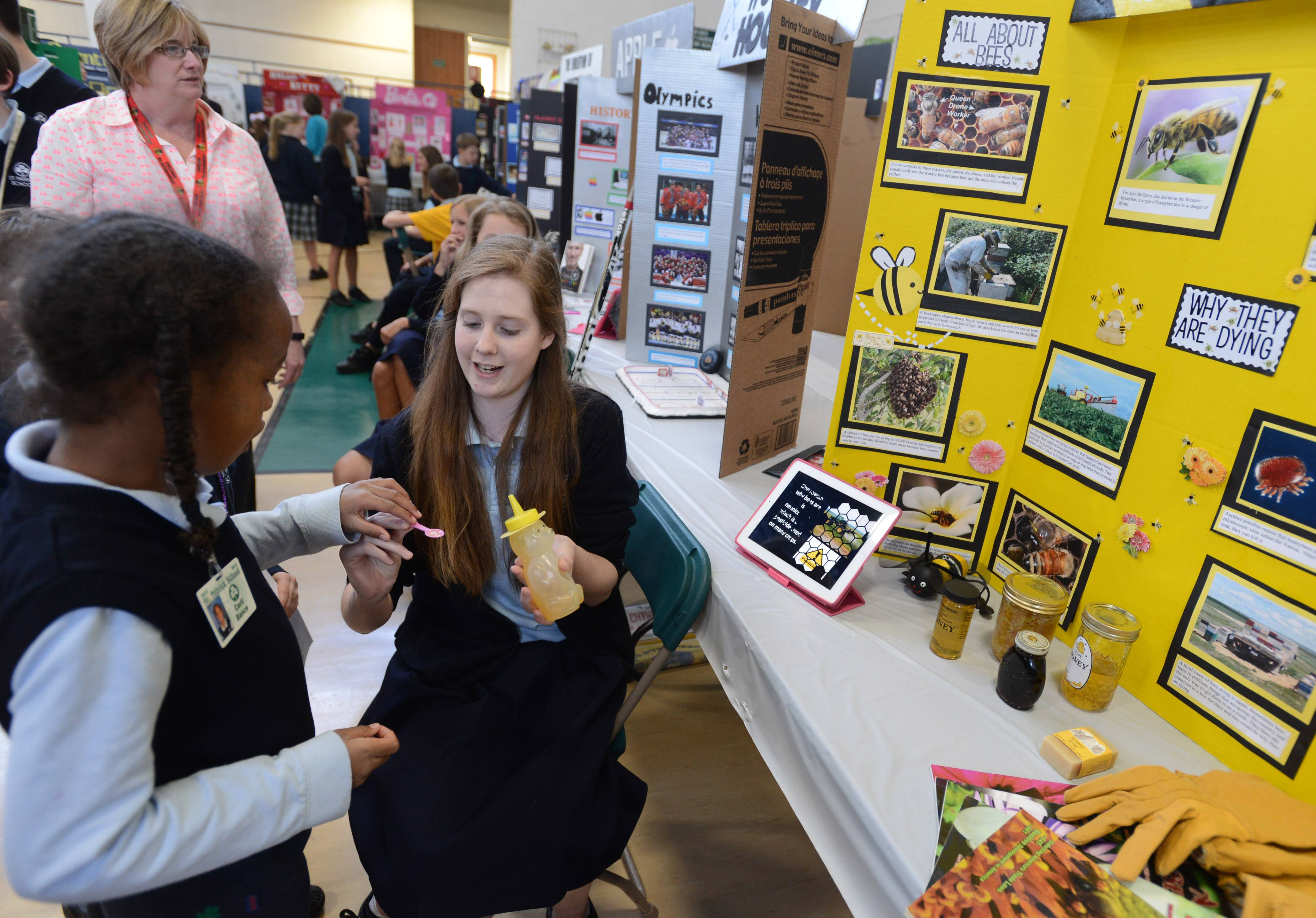 St. Patrick School eighth-grade student Adie Morrill hands out samples of honey for her honey bee project at Wednesday's Academic Fair in Wadsworth.