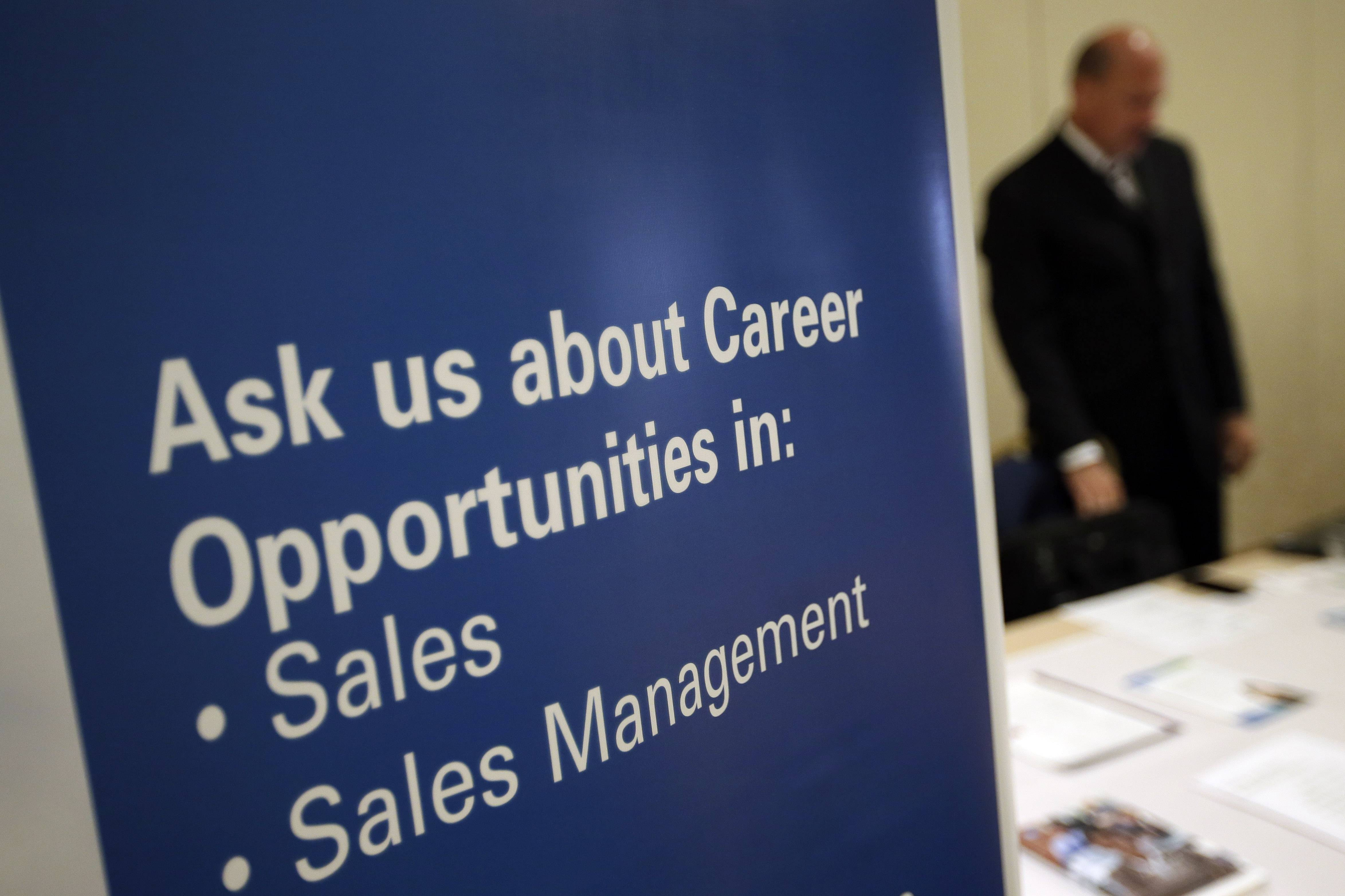 Arecruiter waits to meet with job seekers at a career fair, in King of Prussia, Pa. The number of people seeking U.S. unemployment benefits dropped to the lowest level in almost seven years, falling 32,000 last week to a seasonally adjusted 300,000.