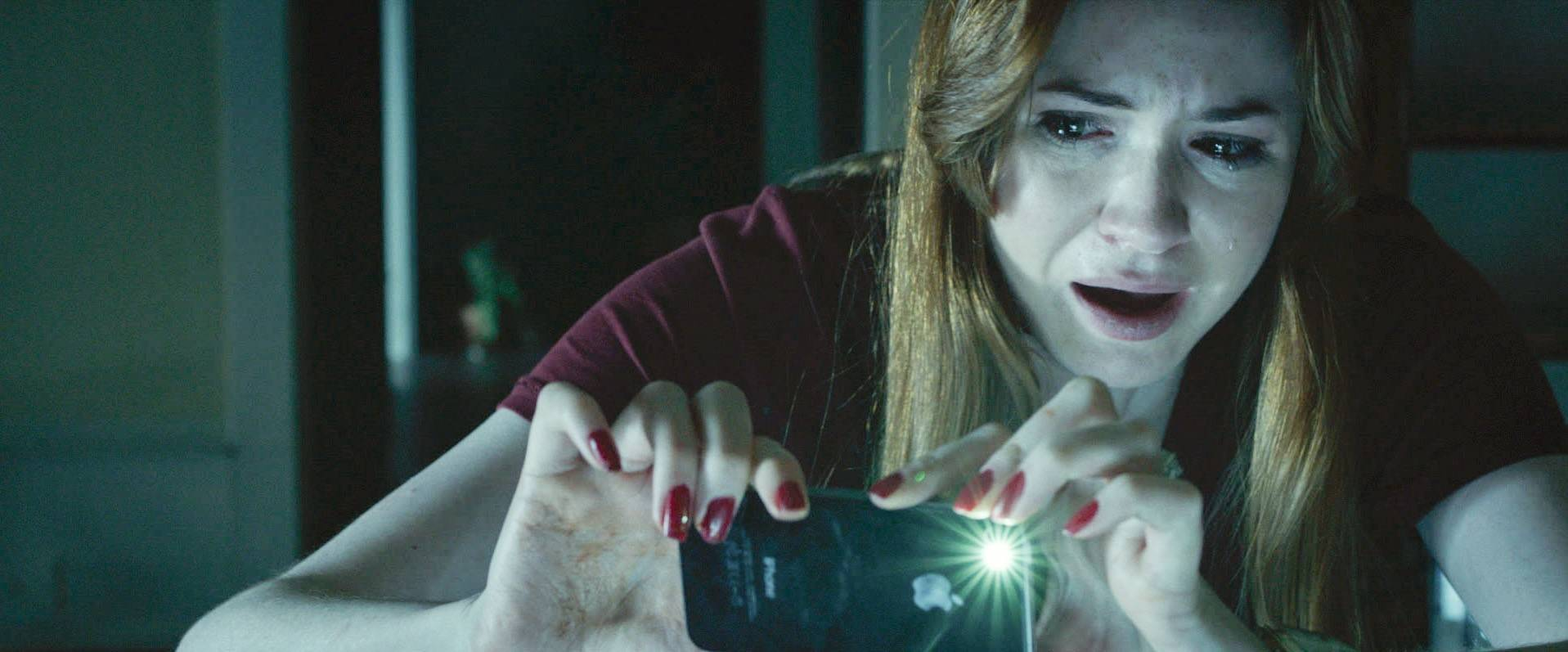 "Kaylie (Karen Gillan) freaks out while investigating a haunted mirror in the supernatural thriller ""Oculus."""