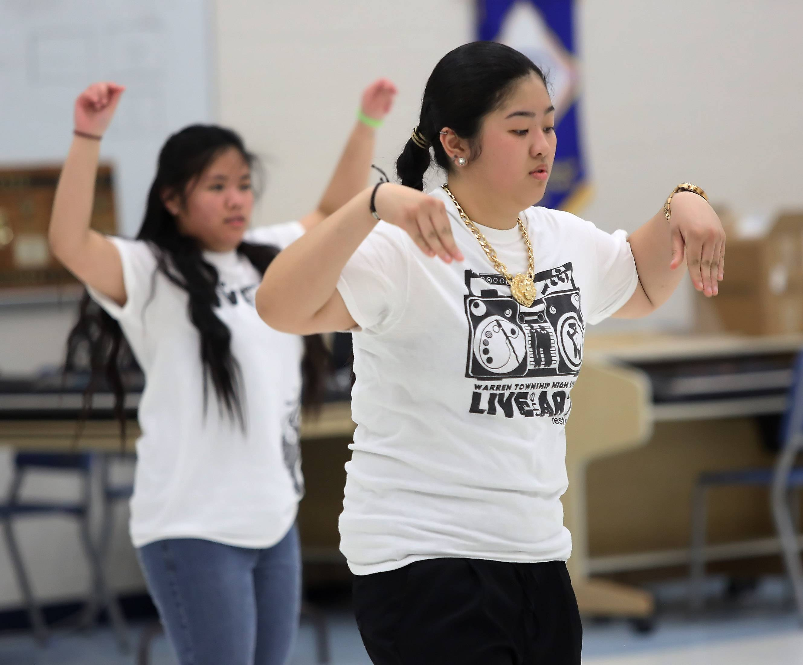 Senior Pauline Galsim, right, and sophomore Tricia Dizon with the group 4-K perform a hip hop routine Thursday during the third annual Live Arts Festival at Warren Township High School at the Almond Road campus in Gurnee.