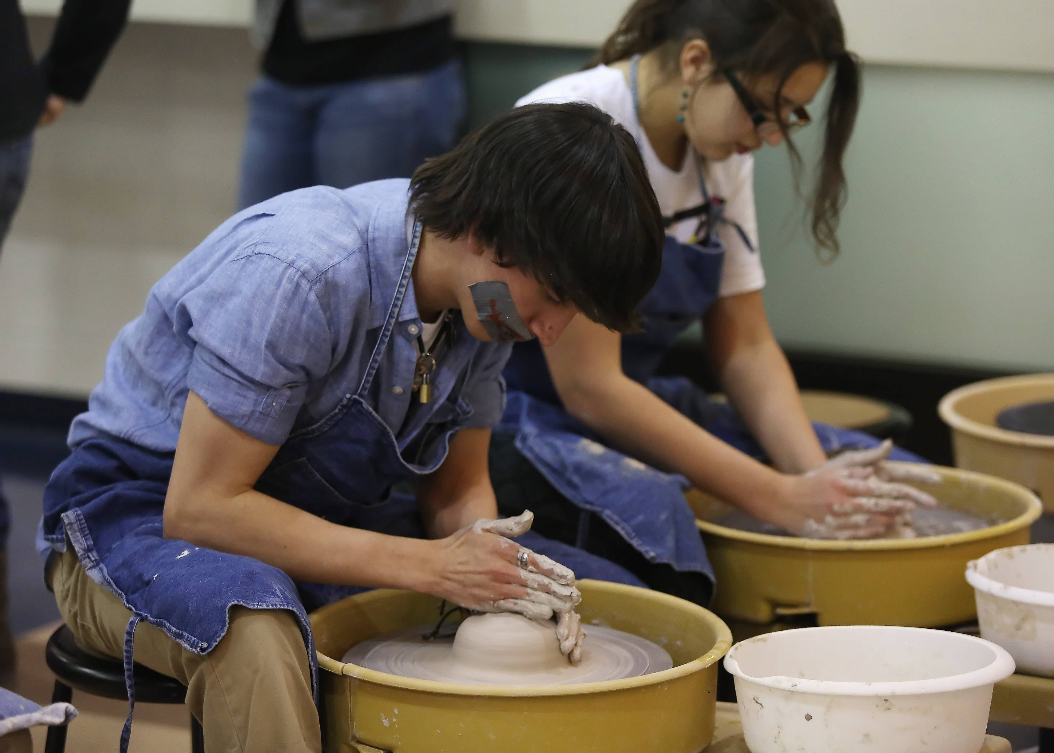 Juniors Damiyen Anderson and Julia Sapyta throw clay pots Thursday during the Live Arts Festival at Warren Township High School at the Almond Road campus in Gurnee.