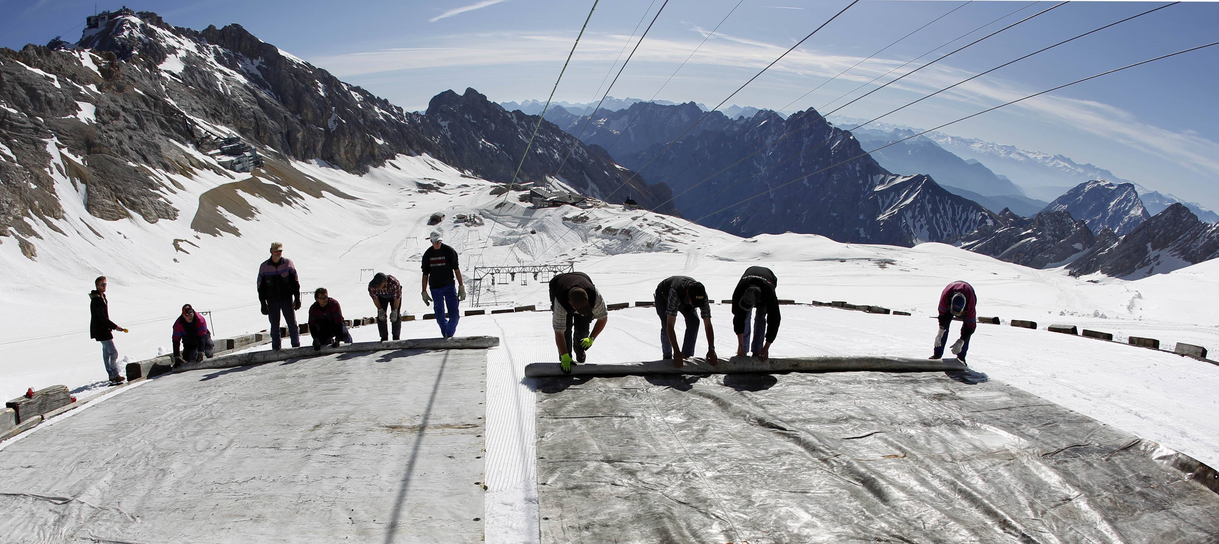 "Workers cover a glacier with oversized plastic sheets on the peak of Germany's highest mountain Zugspitze in this file photo from 2011. The sheets are meant to keep the glacier from melting during the summer months. It's asn example of ""Plan B"" in the fight against climate change."