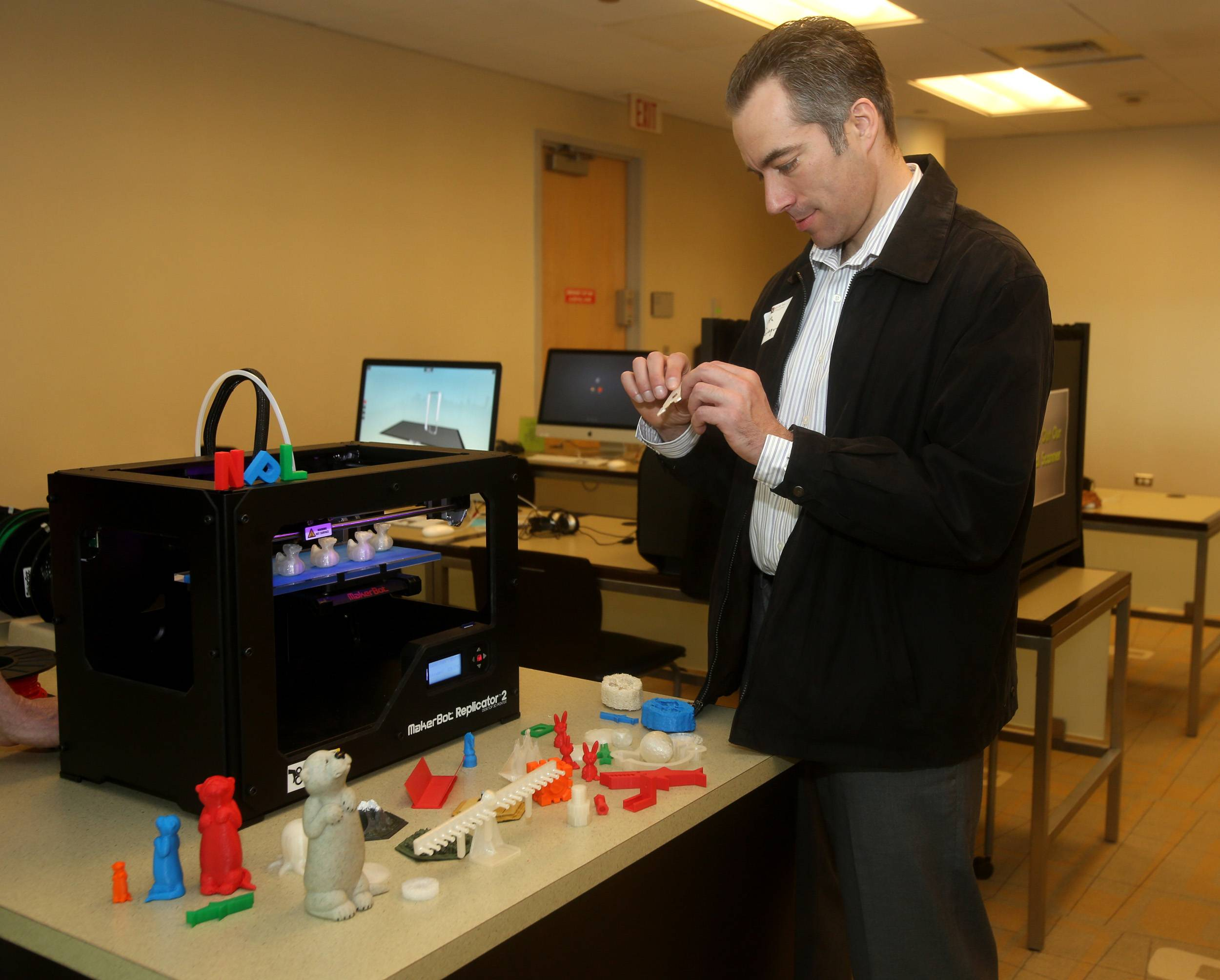 Keith Giaquinto, a chiropractor who toured the 95th Street Library's new Idea Lab on Thursday morning in Naperville with other members of the Naperville Area Chamber of Commerce, examines figurines created by a MakerBot 3-D printer the library bought for about $1,600.